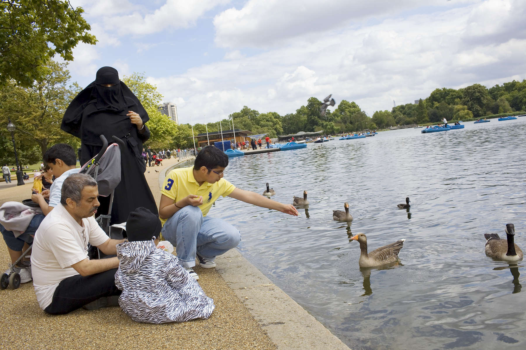 An Arab family feed the birds on the Serpentine Lake in Hyde Park.Arabs have been visiting London for centuries and around 300,000 Arabs have chosen to make the capital their home and a further half a million throughout the UK. The number swells significantly from visitors during the summer. Saudi Arabians spend the most on property in London choosing Belgravia, Kenington, Knightsbridge and Holland Park. Arab culture continues to increase in visibility throughout the capital as integration into this most transient of city's continues.©Peter Dench/Reportage by Getty Images