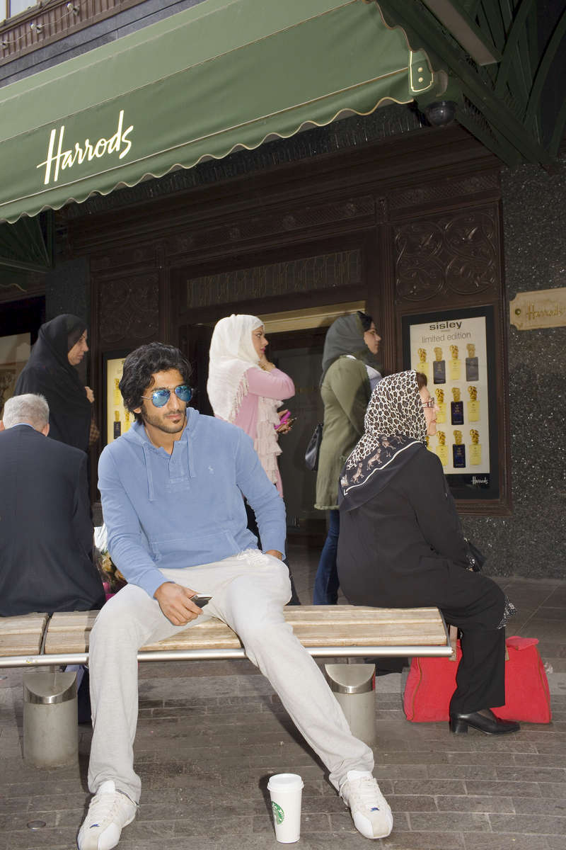 An Arab man sits outside Harrod's store in Knightsbridge, London. Owned by The Qatar Holding Group the famous store is popular with wealthy Arabs.Arabs have been visiting London for centuries and around 300,000 Arabs have chosen to make the capital their home and a further half a million throughout the UK. The number swells significantly from visitors during the summer. Saudi Arabians spend the most on property in London choosing Belgravia, Kenington, Knightsbridge and Holland Park. Arab culture continues to increase in visibility throughout the capital as integration into this most transient of city's continues.©Peter Dench/Reportage by Getty Images