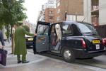 An Arab woman exits a black London taxi helped by a Harrod's doorman.The Knightsbrdige district store Harrods owned by the Qatar Holding Group is a popular shopping destination for Arabs in London.Arabs have been visiting London for centuries and around 300,000 Arabs have chosen to make the capital their home and a further half a million throughout the UK. The number swells significantly from visitors during the summer. Saudi Arabians spend the most on property in London choosing Belgravia, Kenington, Knightsbridge and Holland Park. Arab culture continues to increase in visibility throughout the capital as integration into this most transient of city's continues.©Peter Dench/Reportage by Getty Images