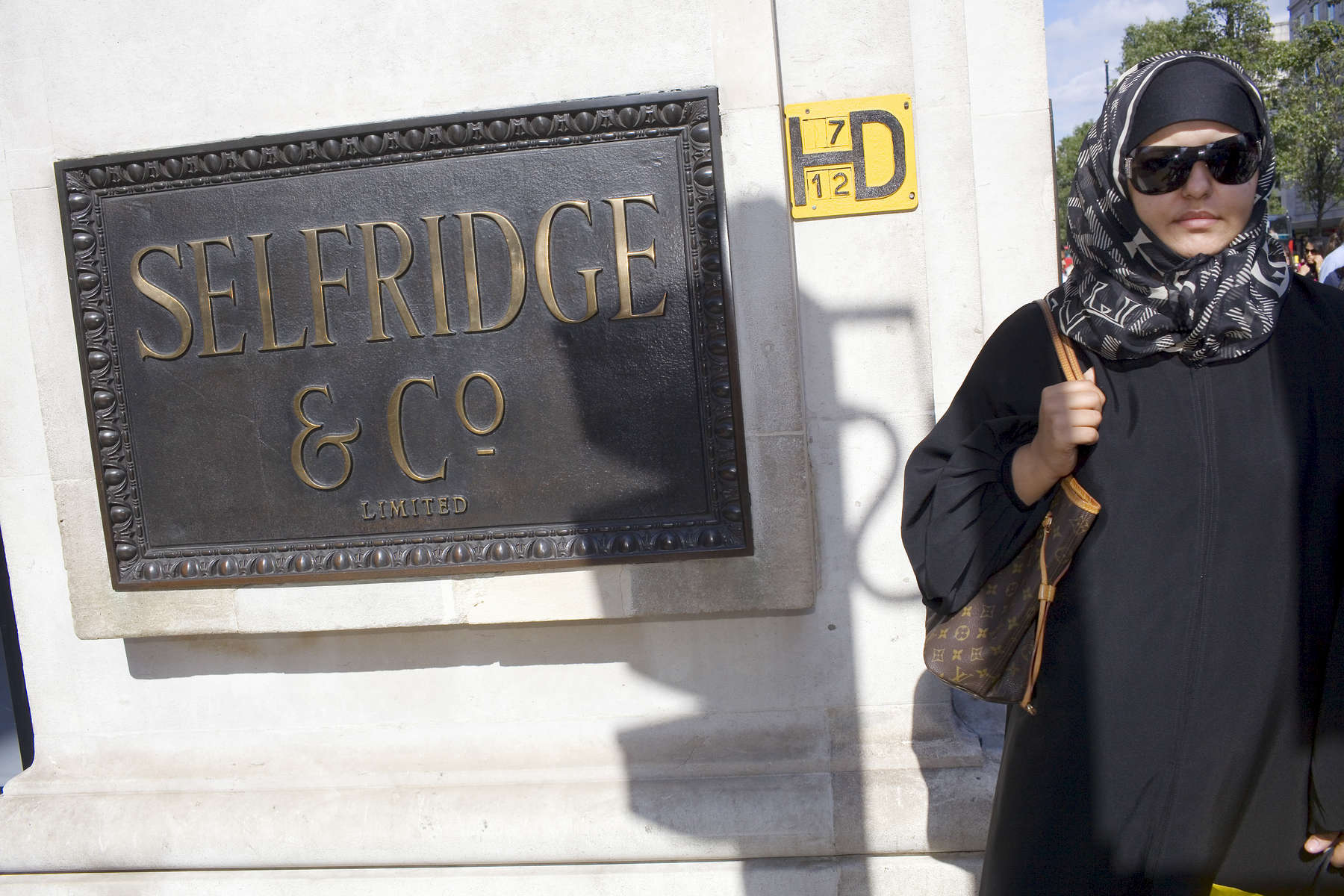 An Arab woman wearing sunglasses passes by the Selfridge & Co store located on London's busy Oxford Street, one of the busiest in Europe.Arabs have been visiting London for centuries and around 300,000 Arabs have chosen to make the capital their home and a further half a million throughout the UK. The number swells significantly from visitors during the summer. Saudi Arabians spend the most on property in London choosing Belgravia, Kenington, Knightsbridge and Holland Park. Arab culture continues to increase in visibility throughout the capital as integration into this most transient of city's continues.©Peter Dench/Reportage by Getty Images