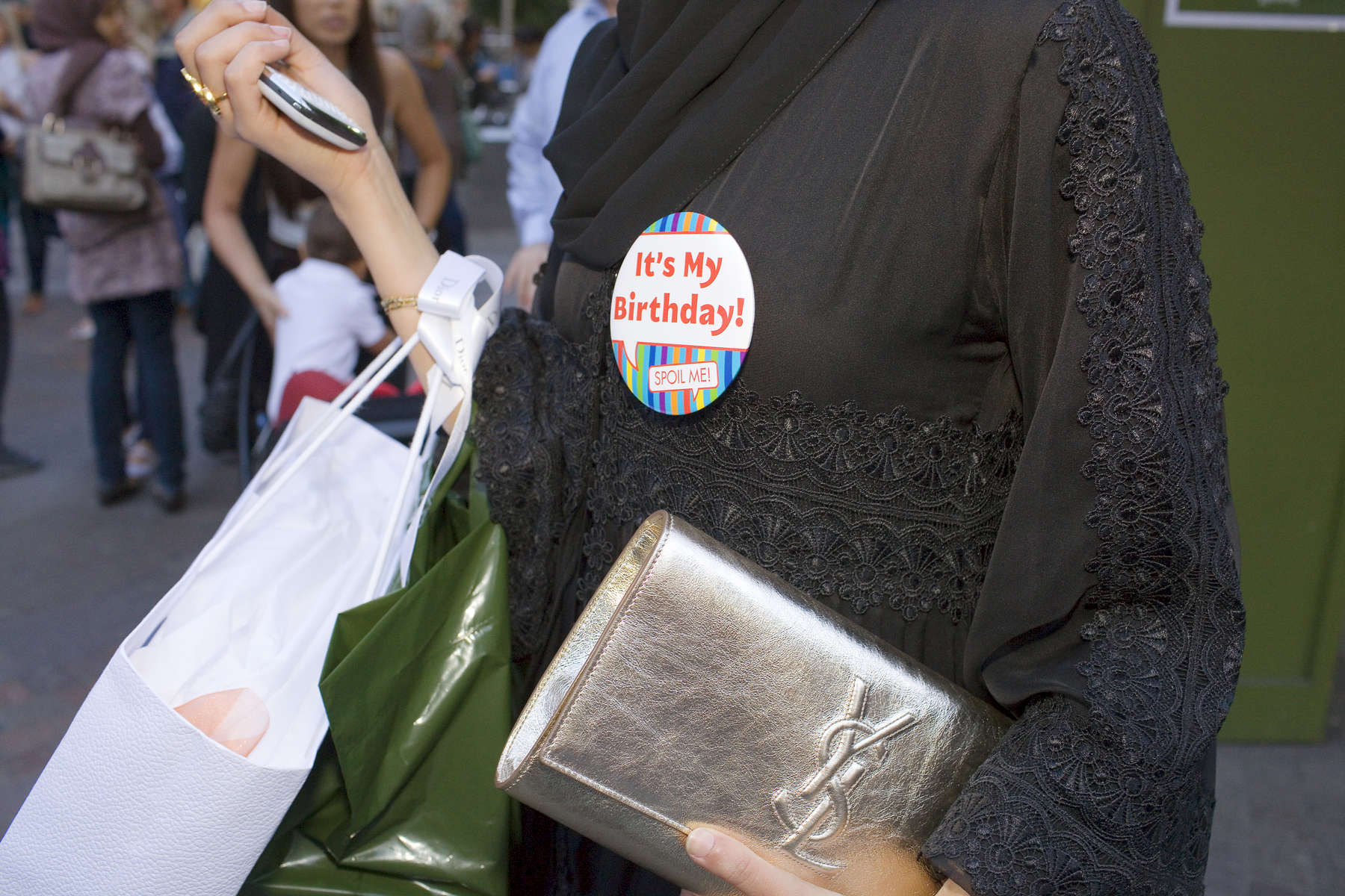 An Arab woman wearing an 'It's Mt Birthday!' badge clutching an Yves Saint Lauren bag and a mobile phone outside Harrod's.The Knightsbrdige district store Harrods owned by the Qatar Holding Group is a popular shopping destination for Arabs in London.Arabs have been visiting London for centuries and around 300,000 Arabs have chosen to make the capital their home and a further half a million throughout the UK. The number swells significantly from visitors during the summer. Saudi Arabians spend the most on property in London choosing Belgravia, Kenington, Knightsbridge and Holland Park. Arab culture continues to increase in visibility throughout the capital as integration into this most transient of city's continues.©Peter Dench/Reportage by Getty Images