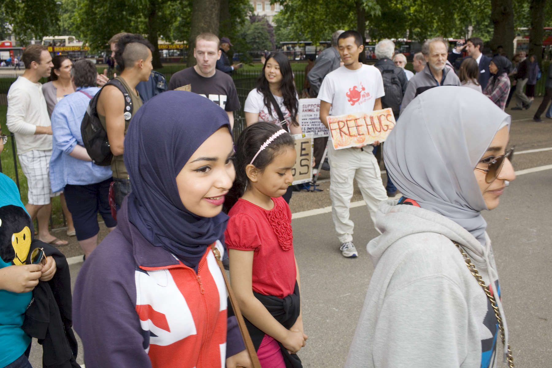 You Arab women pass a man offering 'FREE HUGS' at speaker's corner in Hyde Park.Arabs have been visiting London for centuries and around 300,000 Arabs have chosen to make the capital their home and a further half a million throughout the UK. The number swells significantly from visitors during the summer. Saudi Arabians spend the most on property in London choosing Belgravia, Kenington, Knightsbridge and Holland Park. Arab culture continues to increase in visibility throughout the capital as integration into this most transient of city's continues.©Peter Dench/Reportage by Getty Images