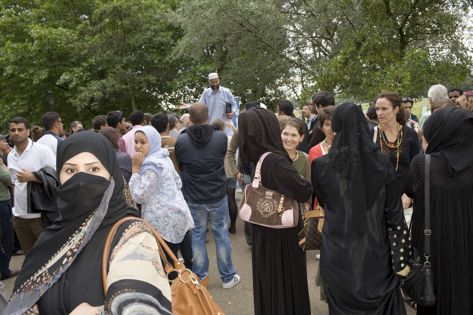 Arab women listen to the various public speaking at Speakers Corner in Hyde Park London.Arabs have been visiting London for centuries and around 300,000 Arabs have chosen to make the capital their home and a further half a million throughout the UK. The number swells significantly from visitors during the summer. Saudi Arabians spend the most on property in London choosing Belgravia, Kenington, Knightsbridge and Holland Park. Arab culture continues to increase in visibility throughout the capital as integration into this most transient of city's continues.©Peter Dench/Reportage by Getty Images