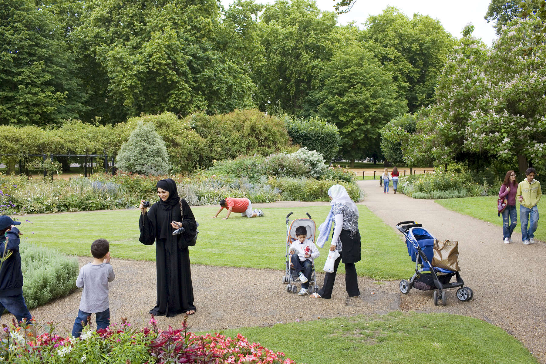 An Arab woman takes photographs in the flower garden at Hyde Park.Arabs have been visiting London for centuries and around 300,000 Arabs have chosen to make the capital their home and a further half a million throughout the UK. The number swells significantly from visitors during the summer. Saudi Arabians spend the most on property in London choosing Belgravia, Kenington, Knightsbridge and Holland Park. Arab culture continues to increase in visibility throughout the capital as integration into this most transient of city's continues.©Peter Dench/Reportage by Getty Images