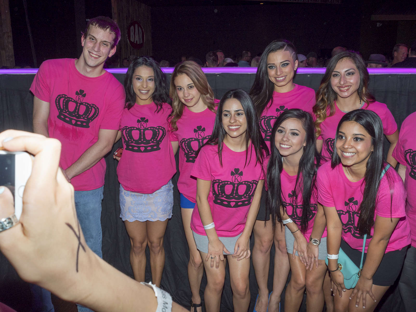 Guests pose for a photograph by the stage at the Twin Peaks 2015 National Bikini Contest where around 68 girls from the USA competed for the crown for Miss Twin Peaks 2015, hosted at Gas Monkey Live, Dallas on the 24th June.Twin Peaks is a chain of sports bars and restaurants (colloquially referred to as breastaurants) based in Dallas, Texas. The chain is known for having its waitresses dress in revealing uniforms that consist of cleavage- and midriff-revealing red plaid (or sometimes black bikini) tops, as well as khaki short shorts. At other times, waitresses wear revealing seasonal or themed outfits. Restaurants are decorated in the theme of a wilderness lodge and serve a mix of American, Southwest and Southern cuisines as well as alcohol. The chain's slogan is {quote}Eats. Drinks. Scenic Views.{quote}Dallas is a major city in Texas and is the largest urban center of the fourth most populous metropolitan area in the United States. The city ranks ninth in the U.S. and third in Texas after Houston and San Antonio. The city's prominence arose from its historical importance as a center for the oil and cotton industries, and its position along numerous railroad lines.For two weeks in the summer of 2015, photographer Peter Dench visited Dallas to document the metroplex in his epic reportage, DENCH DOES DALLAS.Photographed using an Olympus E-M5 Mark II©Peter Dench/Getty Images Reportage