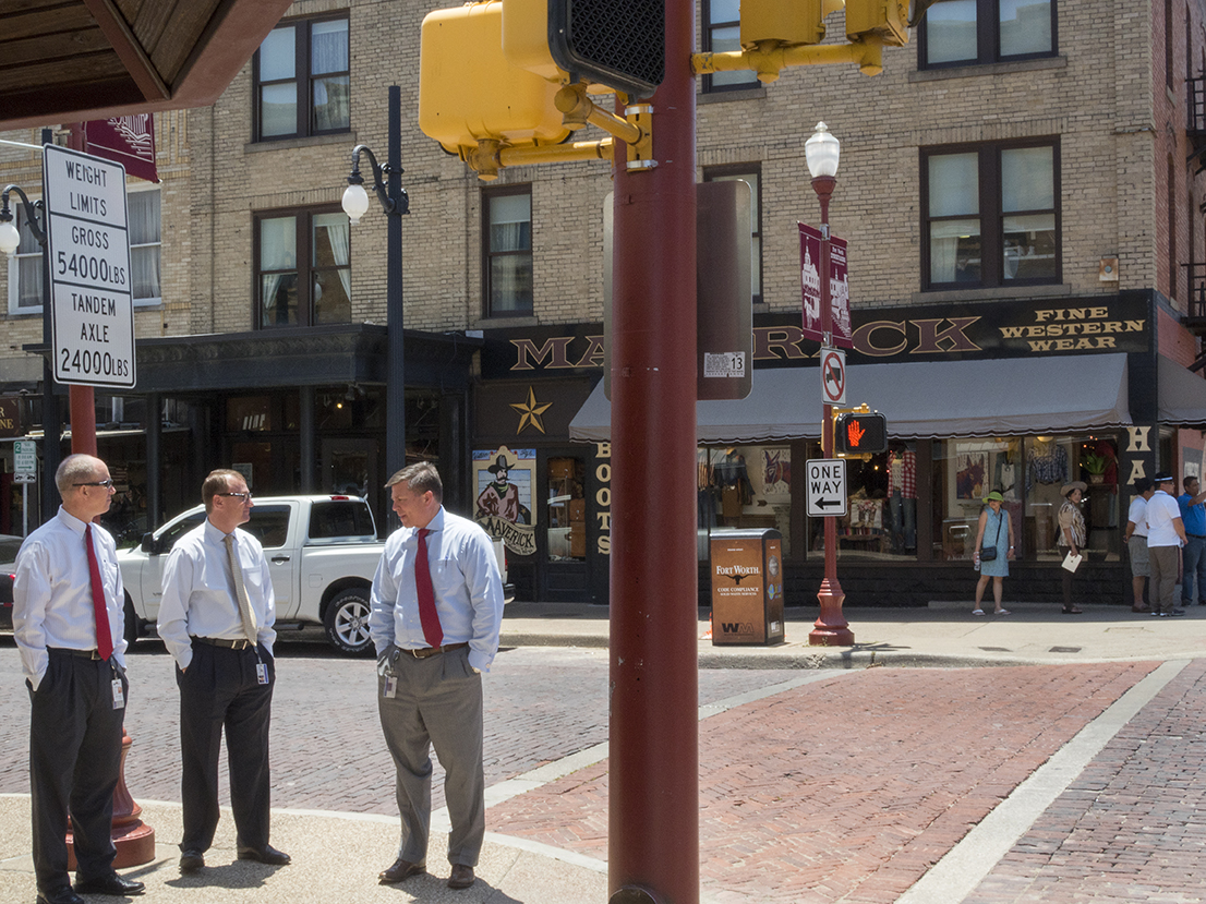 'FINE WESTERN WEAR' Businessmen chat on the corner of a street in the Stockyards district of Fort Worth.The Fort Worth Stockyards is a historic district that is located in Fort Worth, Texas, north of the central business district. The 98-acre (40 ha) district was listed on the National Register of Historic Places as Fort Worth Stockyards Historic District in 1976.They are a former livestock market which operated under various owners from 1866.Dallas is a major city in Texas and is the largest urban center of the fourth most populous metropolitan area in the United States. The city ranks ninth in the U.S. and third in Texas after Houston and San Antonio. The city's prominence arose from its historical importance as a center for the oil and cotton industries, and its position along numerous railroad lines.For two weeks in the summer of 2015, photographer Peter Dench visited Dallas to document the metroplex in his epic reportage, DENCH DOES DALLAS.Photographed using an Olympus E-M5 Mark II©Peter Dench/Getty Images Reportage