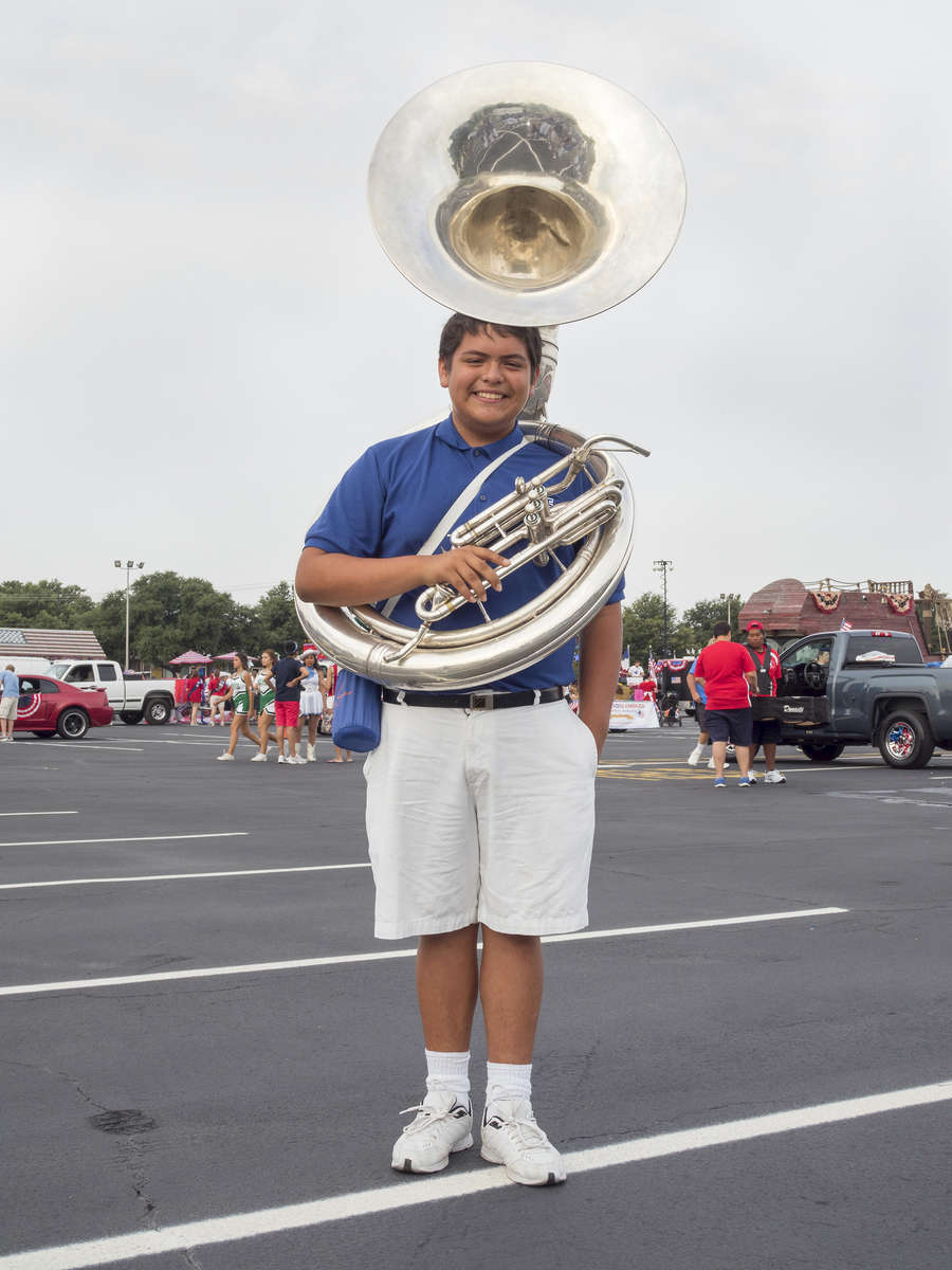 15 year old band member Octavio, on the morning of the 4th July Independence Day parade in Arlington, a city 20 miles west of downtown Dallas.Dallas is a major city in Texas and is the largest urban center of the fourth most populous metropolitan area in the United States. The city ranks ninth in the U.S. and third in Texas after Houston and San Antonio. The city's prominence arose from its historical importance as a center for the oil and cotton industries, and its position along numerous railroad lines.For two weeks in the summer of 2015, photographer Peter Dench visited Dallas to document the metroplex in his epic reportage, DENCH DOES DALLAS.Photographed using an Olympus E-M5 Mark II©Peter Dench/Getty Images Reportage