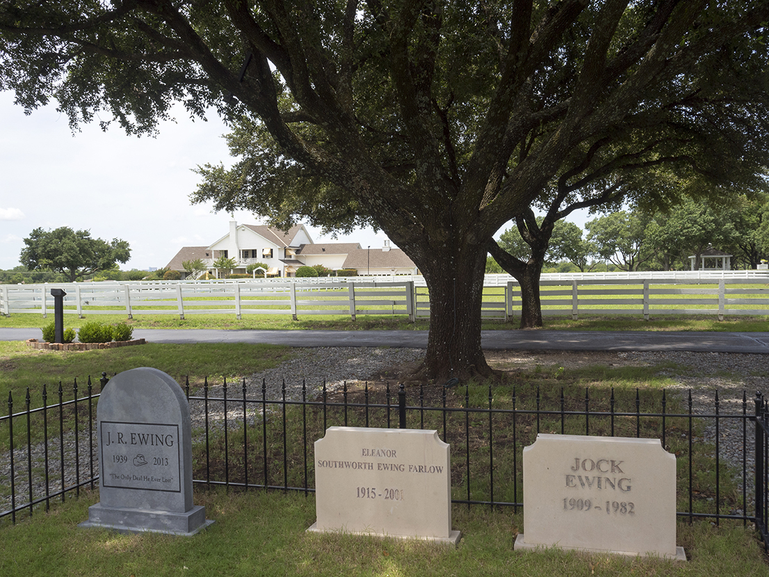 The gravestones of fictional characters J. R. & Jock Ewing & Miss Ellie in the grounds of Southfork ranch.Dallas was a long-running American prime time television soap opera that aired from April 2, 1978, to May 3, 1991, on CBS. The series revolves around a wealthy and feuding Texan family, the Ewings, who own the independent oil company Ewing Oil and the cattle-ranching land of Southfork.Dallas is a major city in Texas and is the largest urban center of the fourth most populous metropolitan area in the United States. The city ranks ninth in the U.S. and third in Texas after Houston and San Antonio. The city's prominence arose from its historical importance as a center for the oil and cotton industries, and its position along numerous railroad lines.For two weeks in the summer of 2015, photographer Peter Dench visited Dallas to document the metroplex in his epic reportage, DENCH DOES DALLAS.Photographed using an Olympus E-M5 Mark II©Peter Dench/Getty Images Reportage