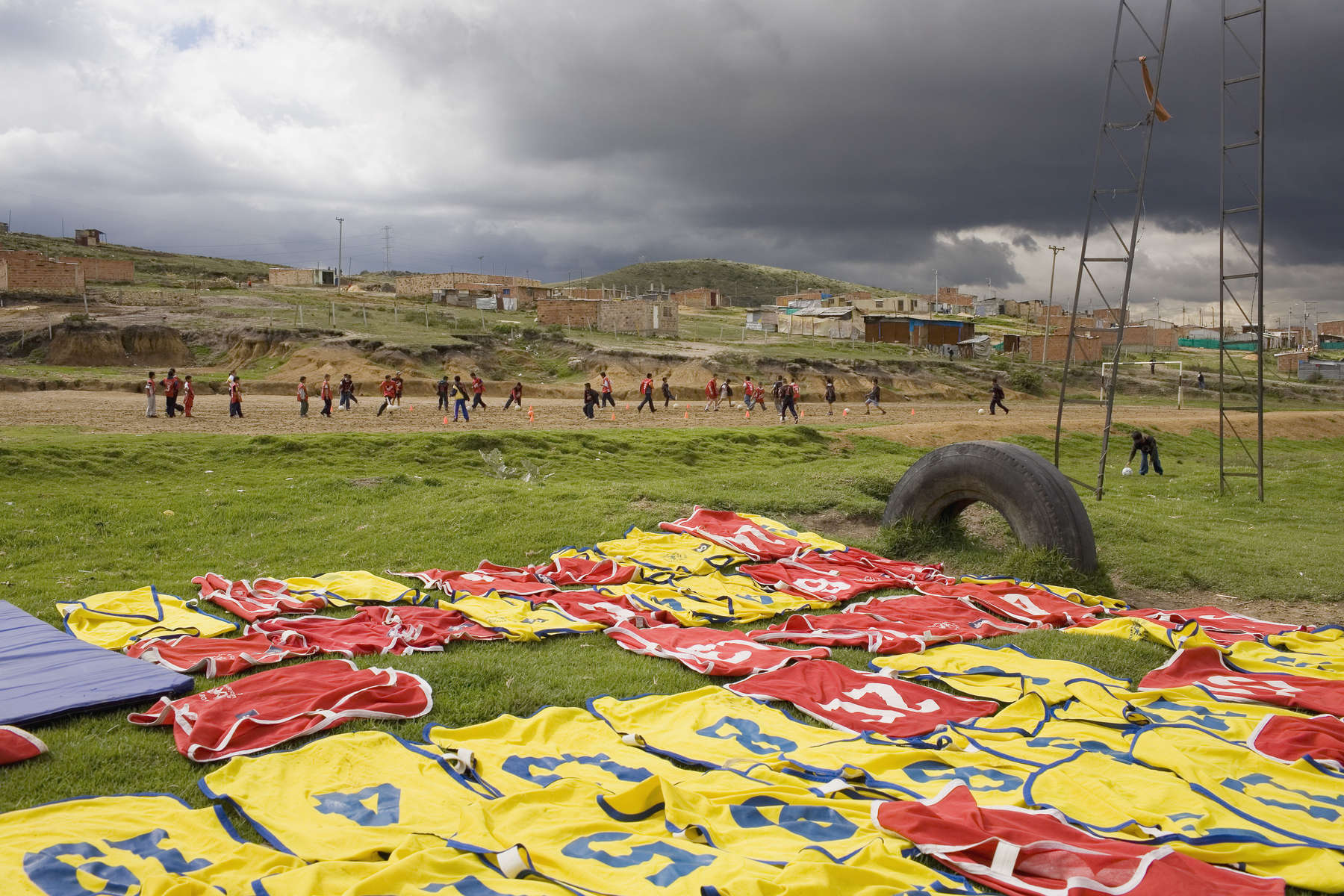 Children on the 'Goals For a Better Life' football programme train on a pitch at the foot of a slum on the outskirts of Colombian capital Bogota. Run by the 'Colombianito's' charity, it aims to use the kids passion for football to keep them in school and away from street gangs.In disaster areas, war zones and urban wastelands, football keeps humanity alive. It brings nations together and promotes unity. It encourages equality and generates pride and self-belief. It has the power to heal and to help, to motivate, to give freedom to dreams and empower a generation. There are millions of people playing the game or helping it to flourish who find that football brings a positive dimension to their lives.Away from the billionaire owned clubs with it's multi-million dollar players, Football's Hidden Story is a series of emotive human interest photographs showing the positive impact football has had at grassroot level on individuals and communities all around the world.