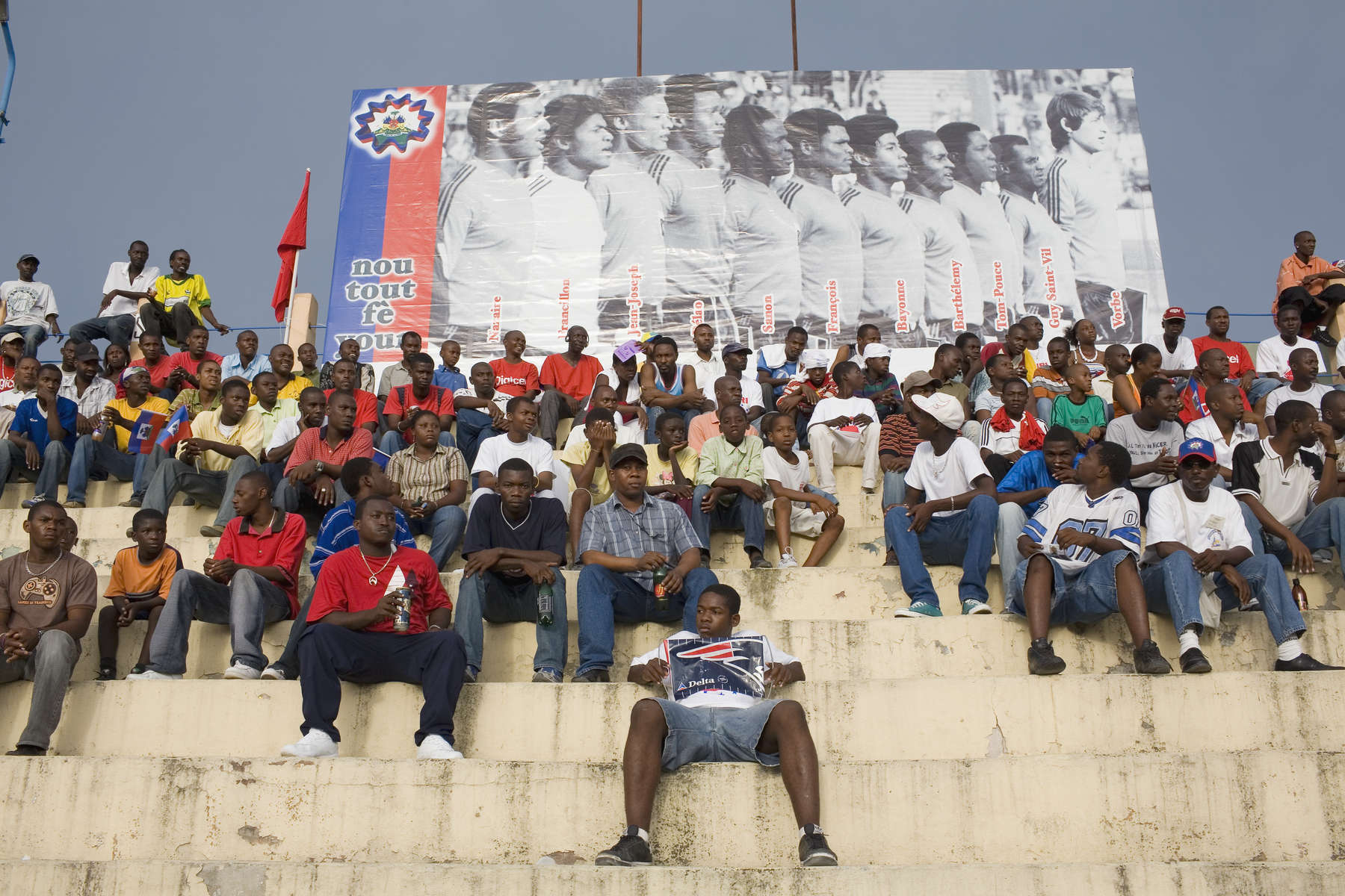 Haitian football fans watch the national under 17 team achieve victory over older boys playing for the USA's Cleveland Cavaliers. The poster shows the team that qualified In 1974 for a place at the World Cup Finals. 33 revolutionary years later the impoverished country's under 17 team played at the FIFA U-17 World Cup Finals in South Korea.In disaster areas, war zones and urban wastelands, football keeps humanity alive. It brings nations together and promotes unity. It encourages equality and generates pride and self-belief. It has the power to heal and to help, to motivate, to give freedom to dreams and empower a generation. There are millions of people playing the game or helping it to flourish who find that football brings a positive dimension to their lives.Away from the billionaire owned clubs with it's multi-million dollar players, Football's Hidden Story is a series of emotive human interest photographs showing the positive impact football has had at grassroot level on individuals and communities all around the world.