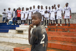 A football team sing inspirational songs from the terraces of the Antoinette Tubman Stadium, Headquarters of the Liberian Football Association. After over a decade of civil war, football is helping bring communities back together.In disaster areas, war zones and urban wastelands, football keeps humanity alive. It brings nations together and promotes unity. It encourages equality and generates pride and self-belief. It has the power to heal and to help, to motivate, to give freedom to dreams and empower a generation. There are millions of people playing the game or helping it to flourish who find that football brings a positive dimension to their lives.Away from the billionaire owned clubs with it's multi-million dollar players, Football's Hidden Story is a series of emotive human interest photographs showing the positive impact football has had at grassroot level on individuals and communities all around the world.