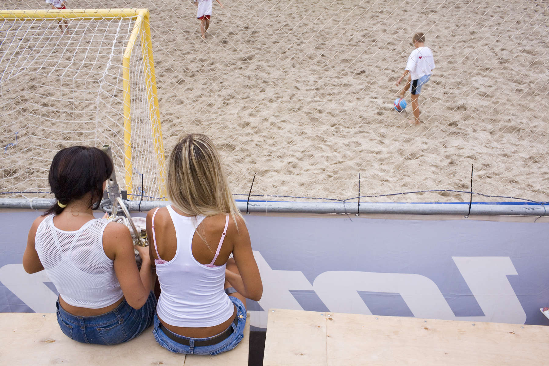 Two beautiful young Ukranian women watch a beach soccer tournament in the capital Kiev. The popularity of beach soccer in the Ukraine has exploded. The national team have become a major force in the game. Not known for it beaches, the Ukraine won their first international title at the May 2007 Euro Beach cup in Spain beating favourites France.In disaster areas, war zones and urban wastelands, football keeps humanity alive. It brings nations together and promotes unity. It encourages equality and generates pride and self-belief. It has the power to heal and to help, to motivate, to give freedom to dreams and empower a generation. There are millions of people playing the game or helping it to flourish who find that football brings a positive dimension to their lives.Away from the billionaire owned clubs with it's multi-million dollar players, Football's Hidden Story is a series of emotive human interest photographs showing the positive impact football has had at grassroot level on individuals and communities all around the world.