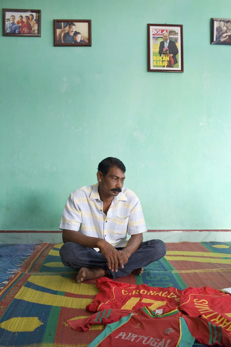 Sarbini in the living room of his Banda Aceh home. The 39 year old lost his wife and daughter when the boxing day Tsunami struck in 2004. His son Martunis survived. He was found 19 days later wandering on the beach wearing the Portuguese national football team shirt. Broadcast images of him inspired players and staff from the team to visit including Cristiano Ronaldo. The house was rebuilt on land purchased from charitable donations.In disaster areas, war zones and urban wastelands, football keeps humanity alive. It brings nations together and promotes unity. It encourages equality and generates pride and self-belief. It has the power to heal and to help, to motivate, to give freedom to dreams and empower a generation. There are millions of people playing the game or helping it to flourish who find that football brings a positive dimension to their lives.Away from the billionaire owned clubs with it's multi-million dollar players, Football's Hidden Story is a series of emotive human interest photographs showing the positive impact football has had at grassroot level on individuals and communities all around the world.