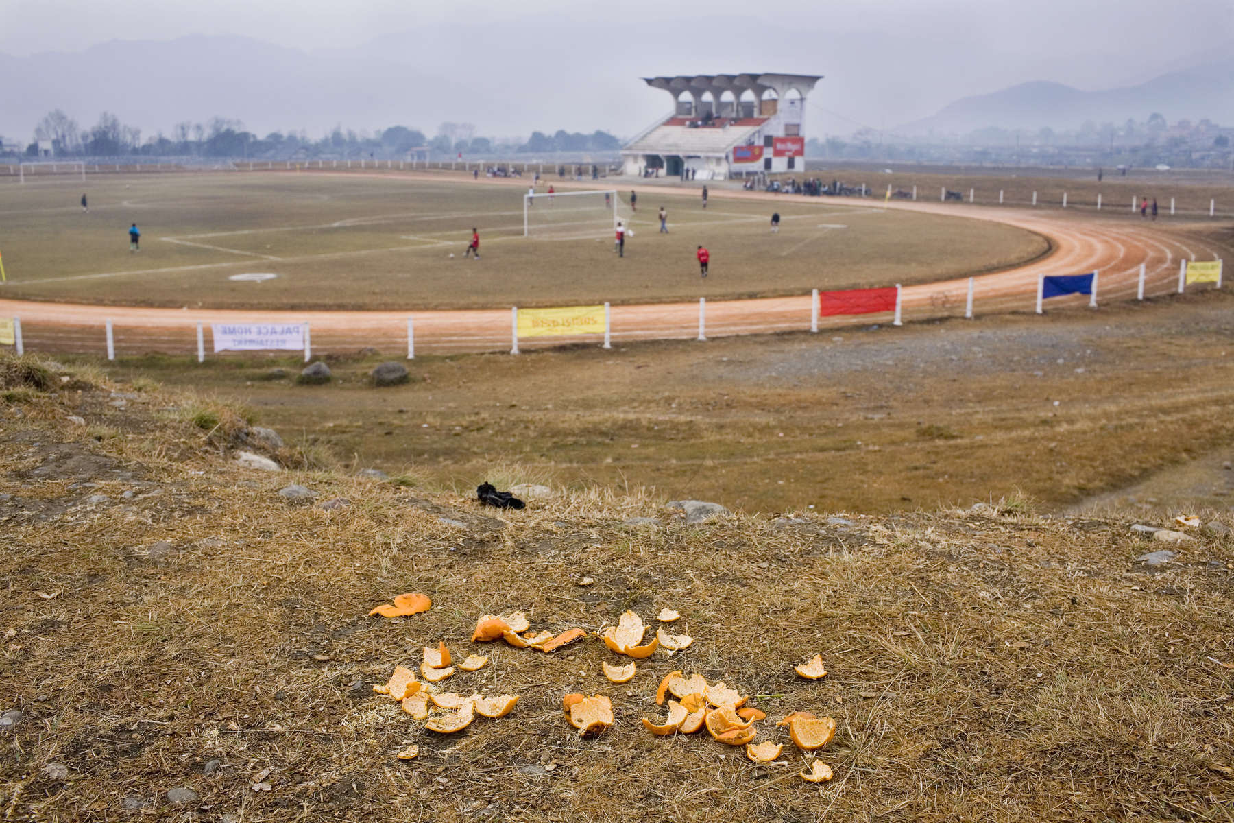 Orange peel scattered on the hill overlooking a football stadium in Pokhara, Nepal.In disaster areas, war zones and urban wastelands, football keeps humanity alive. It brings nations together and promotes unity. It encourages equality and generates pride and self-belief. It has the power to heal and to help, to motivate, to give freedom to dreams and empower a generation. There are millions of people playing the game or helping it to flourish who find that football brings a positive dimension to their lives.Away from the billionaire owned clubs with it's multi-million dollar players, Football's Hidden Story is a series of emotive human interest photographs showing the positive impact football has had at grassroot level on individuals and communities all around the world.