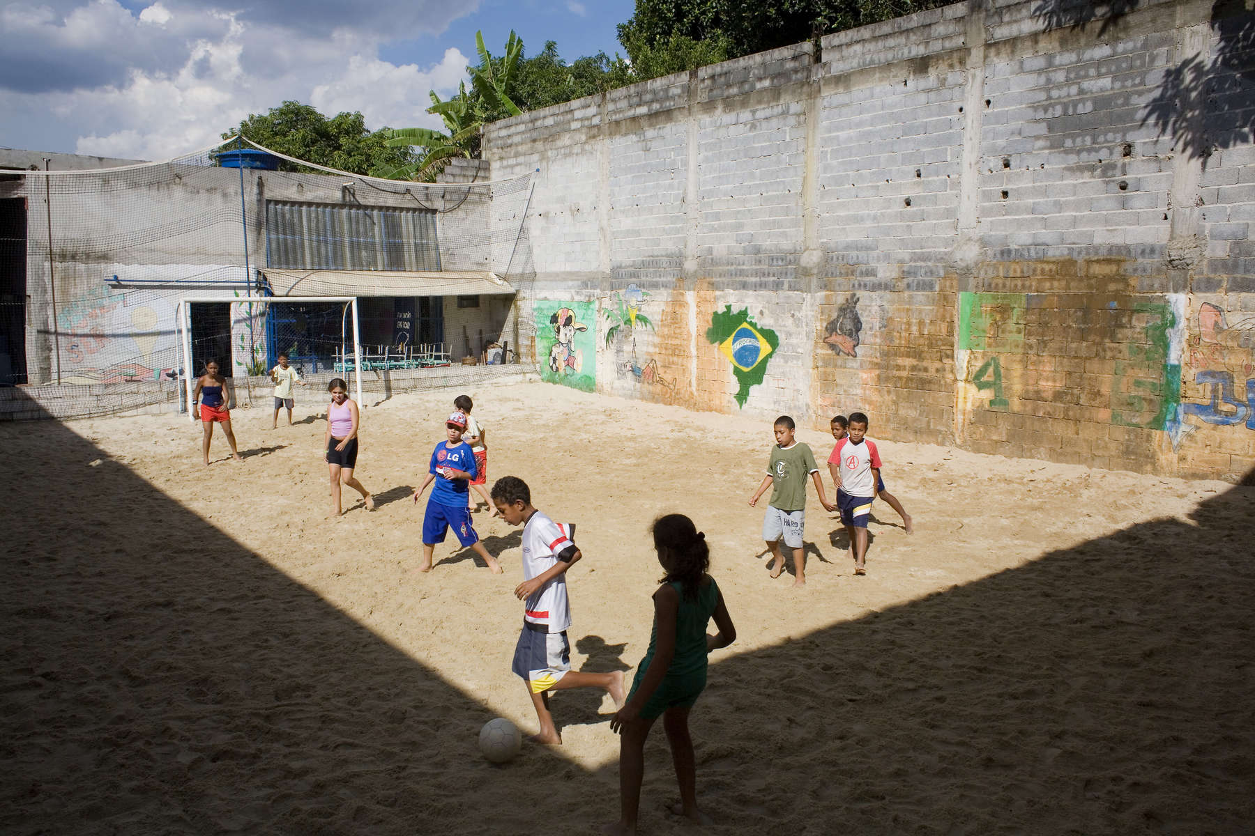 Brazilian kids play beach football at the EPROCAD centre in Sao Paulo. Football is used to transform chldren with low self esteem and negative perception into critical proactive citizens.In disaster areas, war zones and urban wastelands, football keeps humanity alive. It brings nations together and promotes unity. It encourages equality and generates pride and self-belief. It has the power to heal and to help, to motivate, to give freedom to dreams and empower a generation. There are millions of people playing the game or helping it to flourish who find that football brings a positive dimension to their lives.Away from the billionaire owned clubs with it's multi-million dollar players, Football's Hidden Story is a series of emotive human interest photographs showing the positive impact football has had at grassroot level on individuals and communities all around the world.