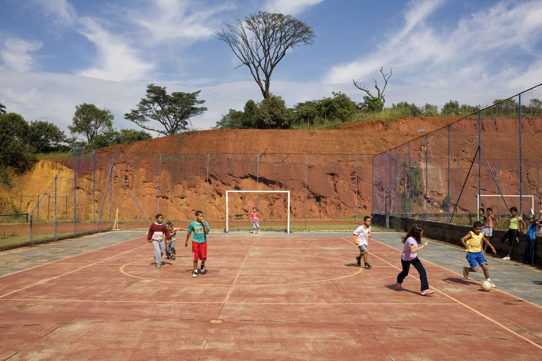 Children play a game of football on the all weather pitch at the EPROCAD centre in Sao Paolo. Football is used to transform childrem with low self esteem and negative perceptions into critical proactive citizens.In disaster areas, war zones and urban wastelands, football keeps humanity alive. It brings nations together and promotes unity. It encourages equality and generates pride and self-belief. It has the power to heal and to help, to motivate, to give freedom to dreams and empower a generation. There are millions of people playing the game or helping it to flourish who find that football brings a positive dimension to their lives.Away from the billionaire owned clubs with it's multi-million dollar players, Football's Hidden Story is a series of emotive human interest photographs showing the positive impact football has had at grassroot level on individuals and communities all around the world.