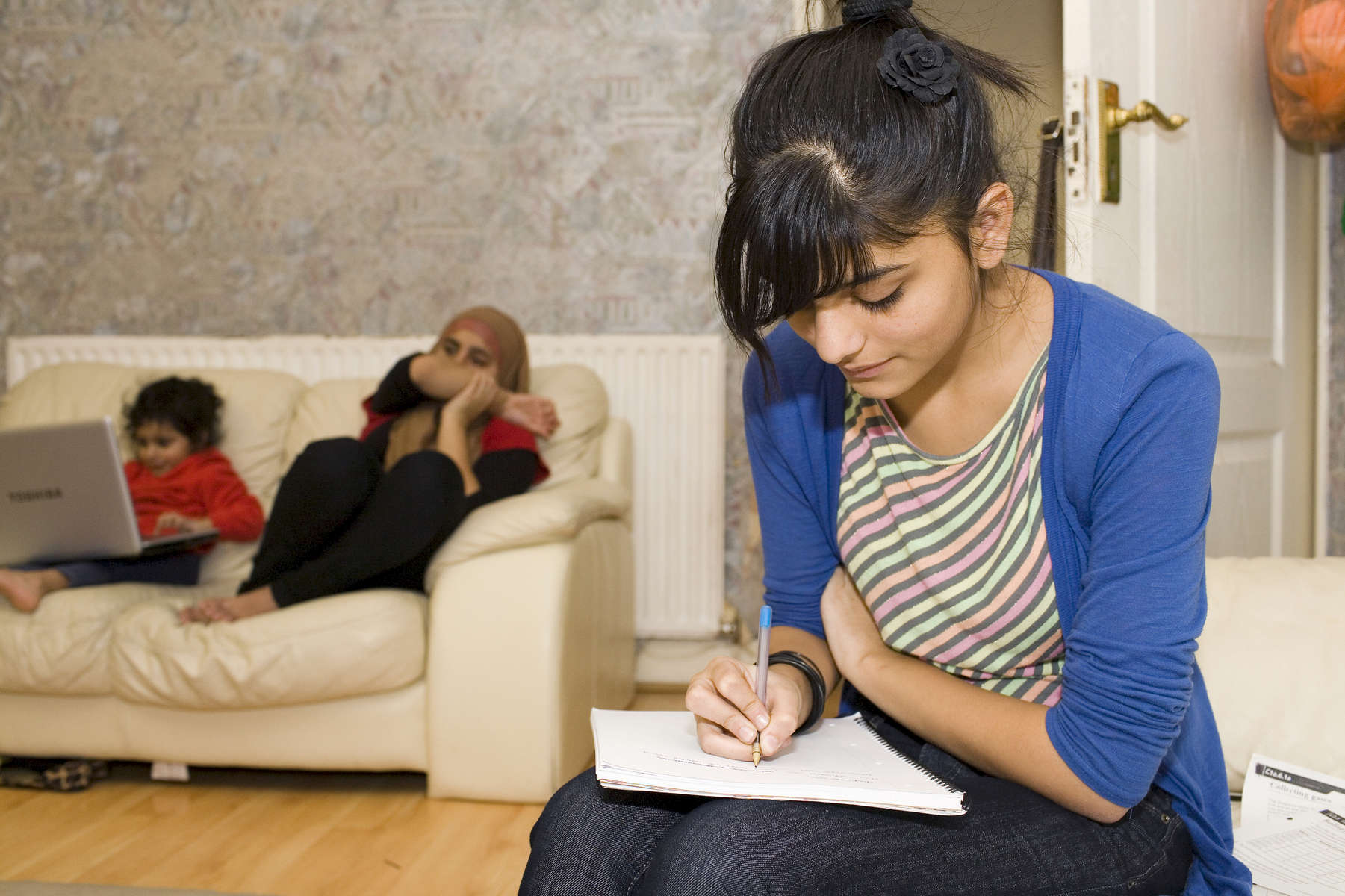 15 year old Laiba Abassi studying for her exams in the living room of the home where she lives with her mother Safia (40), father Khalid (43) and sisters Maira (14 pictured centre), Ahareem (10) and Fatimah (3 pictured left). Laiba is a 2nd generation migrant from Pakistan. Her mother arrived from the capital Islamabad aged 3 in 1972, her father arrived in 1995. It is a three bedroom home, Laiba and her parents each have one, her three siblings share the other all sleeping in one big bed.Villiers High School is in the town of Southall. It has a very wide ethnic diversity. 45 different 1st spoken languages are listed among the 1208 pupils. 25 ethnic groups are represented with Indian, Pakistani and Black-Somali the three highest.Southall is a suburban district of West London, England. The town has one of the largest concentrations of South Asian people outside of the Indian sub-continent. Over 55% os Southall's population of 70,000 is Indian/Pakistani, with less than 10% being White British.