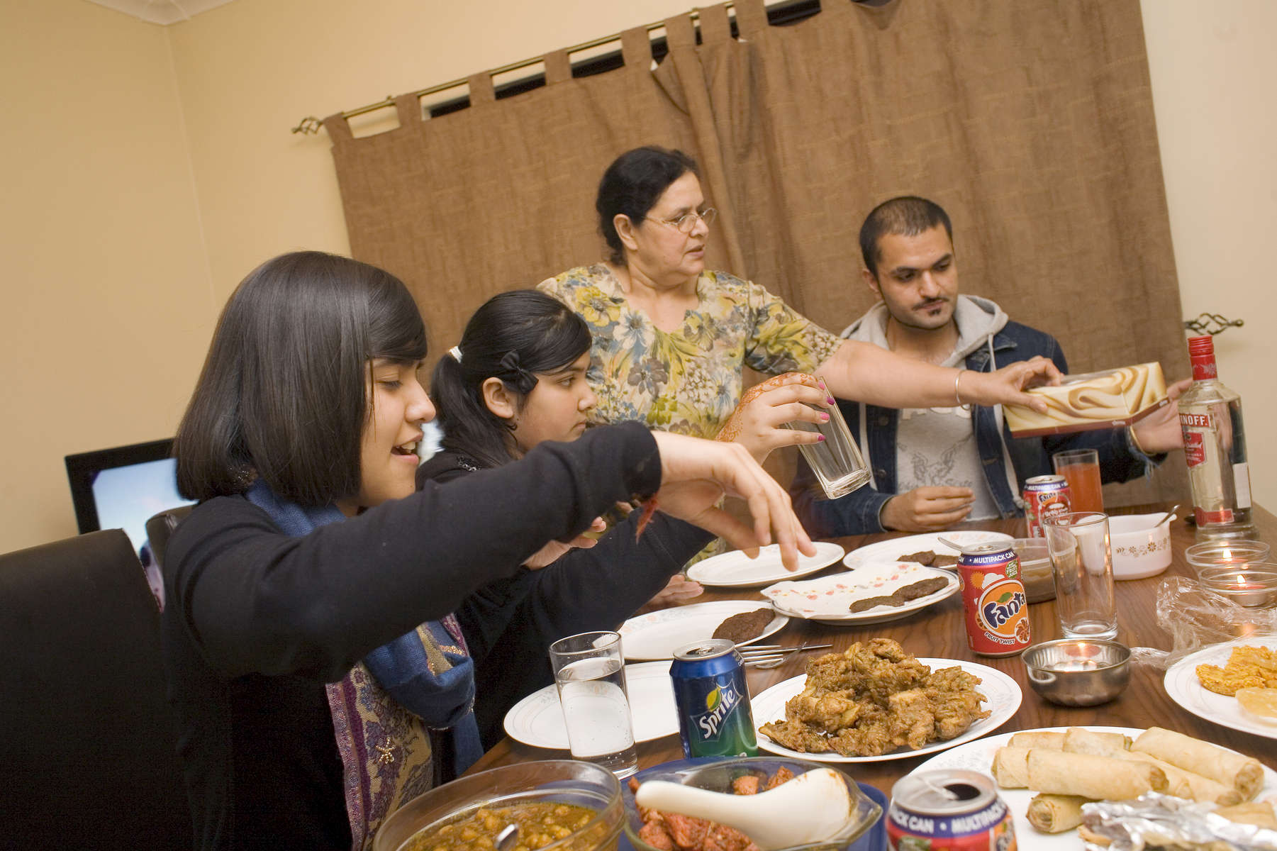 15 year old Robyn Kullar (left) with her sister Alisha (13), grandmother Kuldeep and Uncle, Blaise. They are having dinner together for Diwali, an important festival in the Sikh calendar. Robyn and Alsiha are pupils at Villiers High School in the town of Southall. It has a very wide ethnic diversity. 45 different 1st spoken languages are listed among the 1208 pupils. 25 ethnic groups are represented with Indian, Pakistani and Black-Somali the three highest.Southall is a suburban district of West London, England. The town has one of the largest concentrations of South Asian people outside of the Indian sub-continent. Over 55% os Southall's population of 70,000 is Indian/Pakistani, with less than 10% being White British.