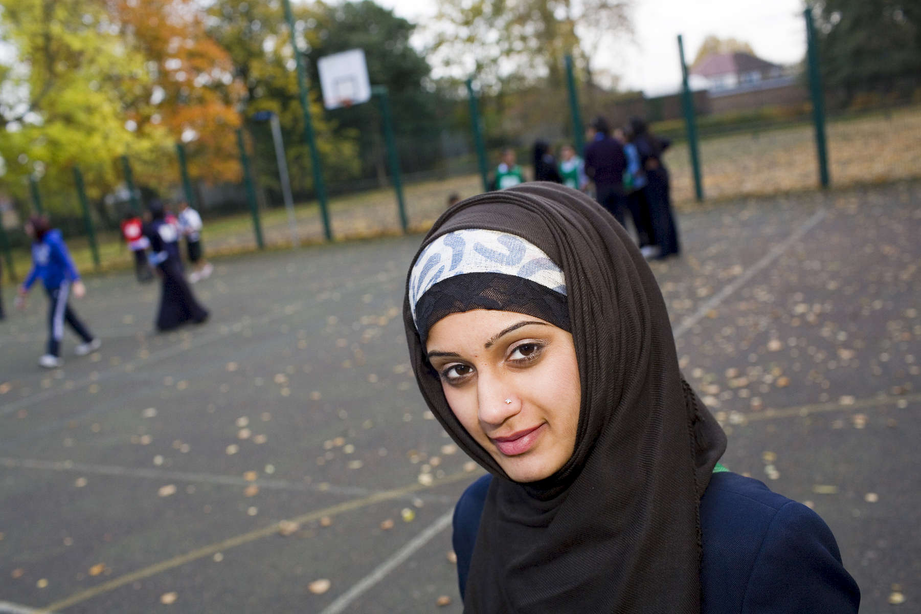 15 year old Muslim, Mahnoor Chaudry at the Tuesday after school netball club at Villiers High School. Mahnoor's father was born in the UK, her mother arrived from Pakistan in the late 1980's.Villiers High School is in the town of Southall. It has a very wide ethnic diversity. 45 different 1st spoken languages are listed among the 1208 pupils. 25 ethnic groups are represented with Indian, Pakistani and Black-Somali the three highest.Southall is a suburban district of West London, England. The town has one of the largest concentrations of South Asian people outside of the Indian sub-continent. Over 55% os Southall's population of 70,000 is Indian/Pakistani, with less than 10% being White British.