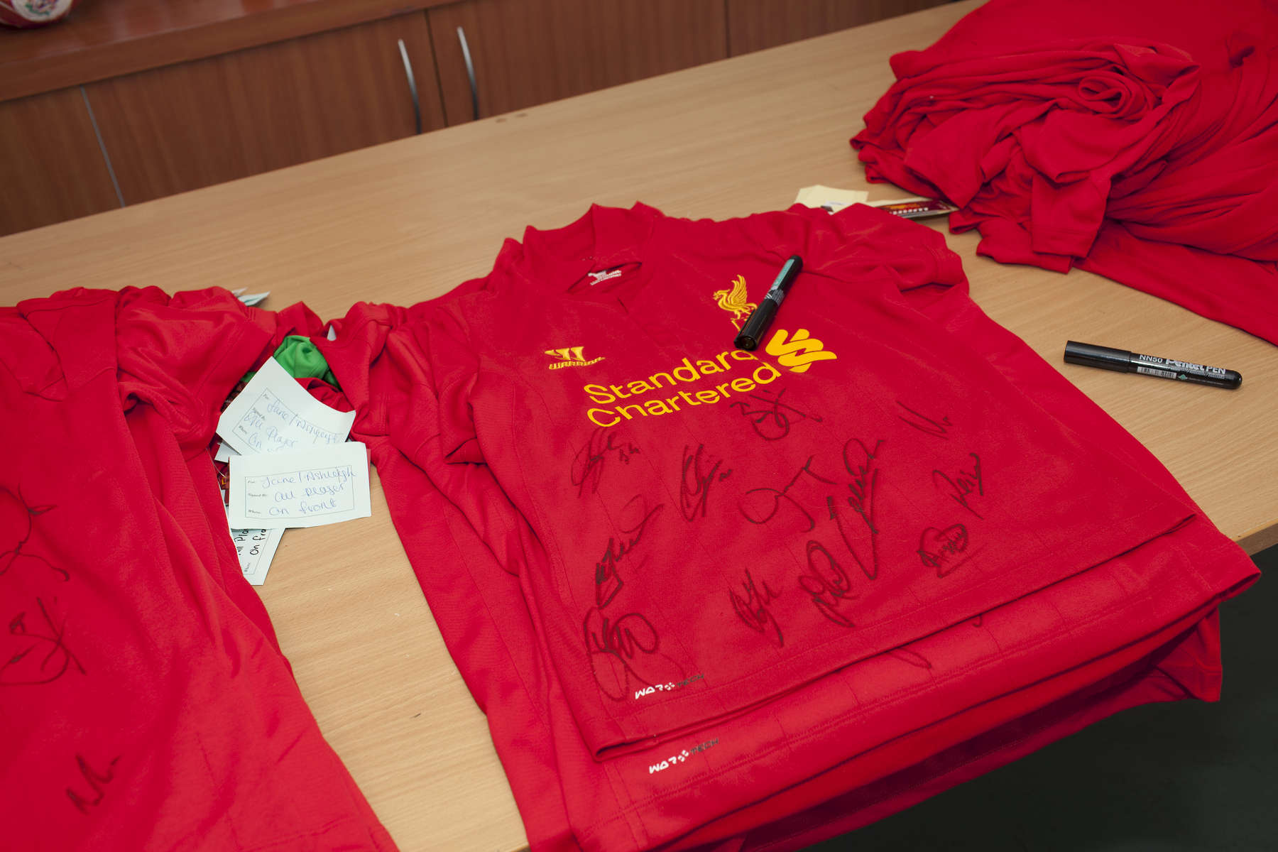 Signed Liverpool FC football shirts in the canteen at Melwood.Melwood is the Liverpool FC training ground, located in the West Derby area of Liverpool. It is seperate from the Liverpool Academy, which is based in Kirkby.Melwood was redeveloped in the early 2000′s with large input from then-manager Gerard Houllier and now features some of the best facilities in Europe. It has been the club's training ground since the fifties and was previously transformed into a top class facility by Bill Shankly.Facilities include sythetic pitches, rehabilitation rooms, press and meeting rooms, gymnasium, swimming pool, restaurant and recreational facilities.