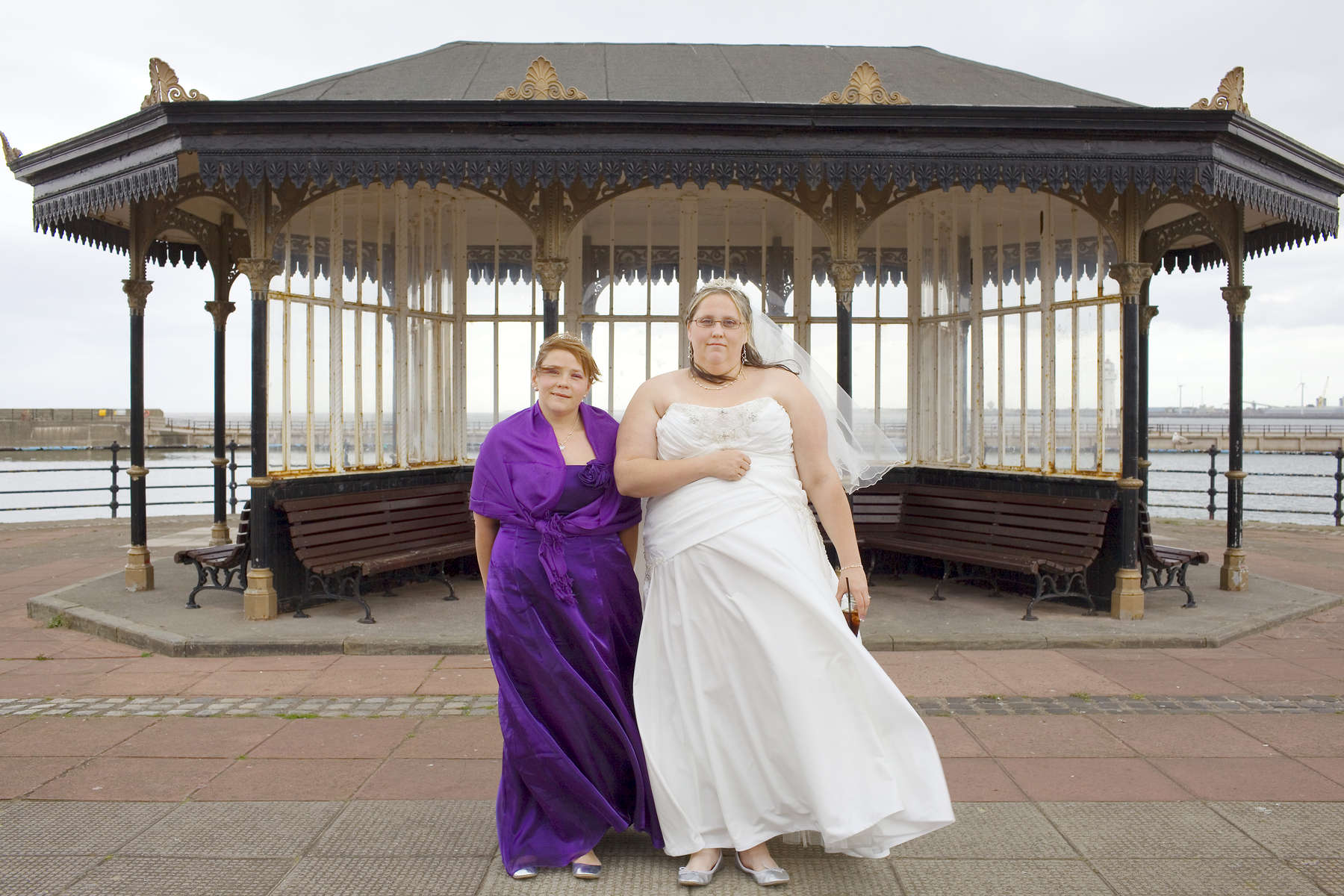 Newly wed Claire Simon-Kind (30) with sister and bridesmaid Sarah Simon (28) in front of a weather shelter on New Brighton promenade.In 1986, world famous photographer Martin Parr published his book 'The Last Resort,' a set of photographs taken over three seasons 1983-85 in the Liverpool suburb of New Brighton. 25 years later, photographer and Parr fan, Peter Dench, went on a Bank Holiday pilgrimage to New Brigthon to walk in Parr's footsteps and document what has changed or remained the same in the seaside town.