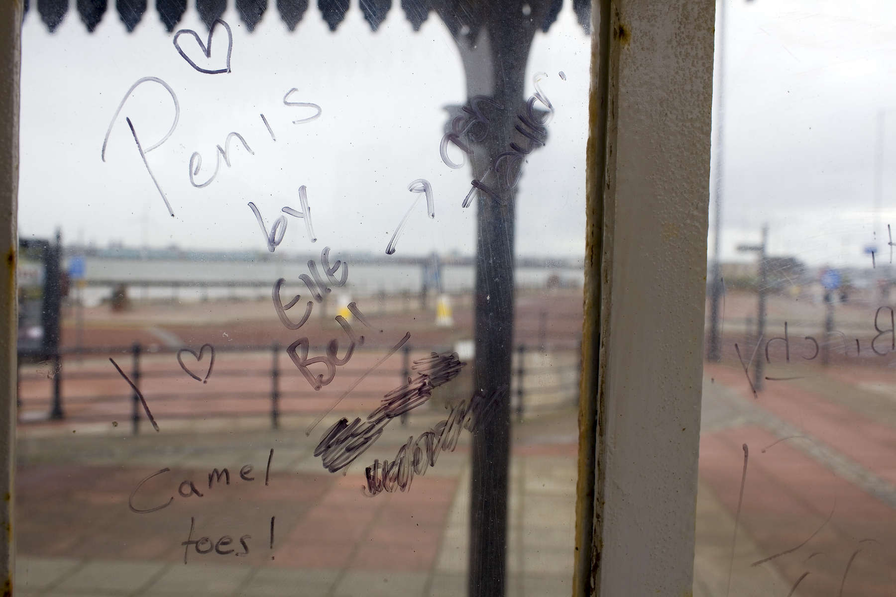 Graffiti penned on the glass of a weather shelter on New Brighton promenade.In 1986, world famous photographer Martin Parr published his book 'The Last Resort,' a set of photographs taken over three seasons 1983-85 in the Liverpool suburb of New Brighton. 25 years later, photographer and Parr fan, Peter Dench, went on a Bank Holiday pilgrimage to New Brigthon to walk in Parr's footsteps and document what has changed or remained the same in the seaside town.