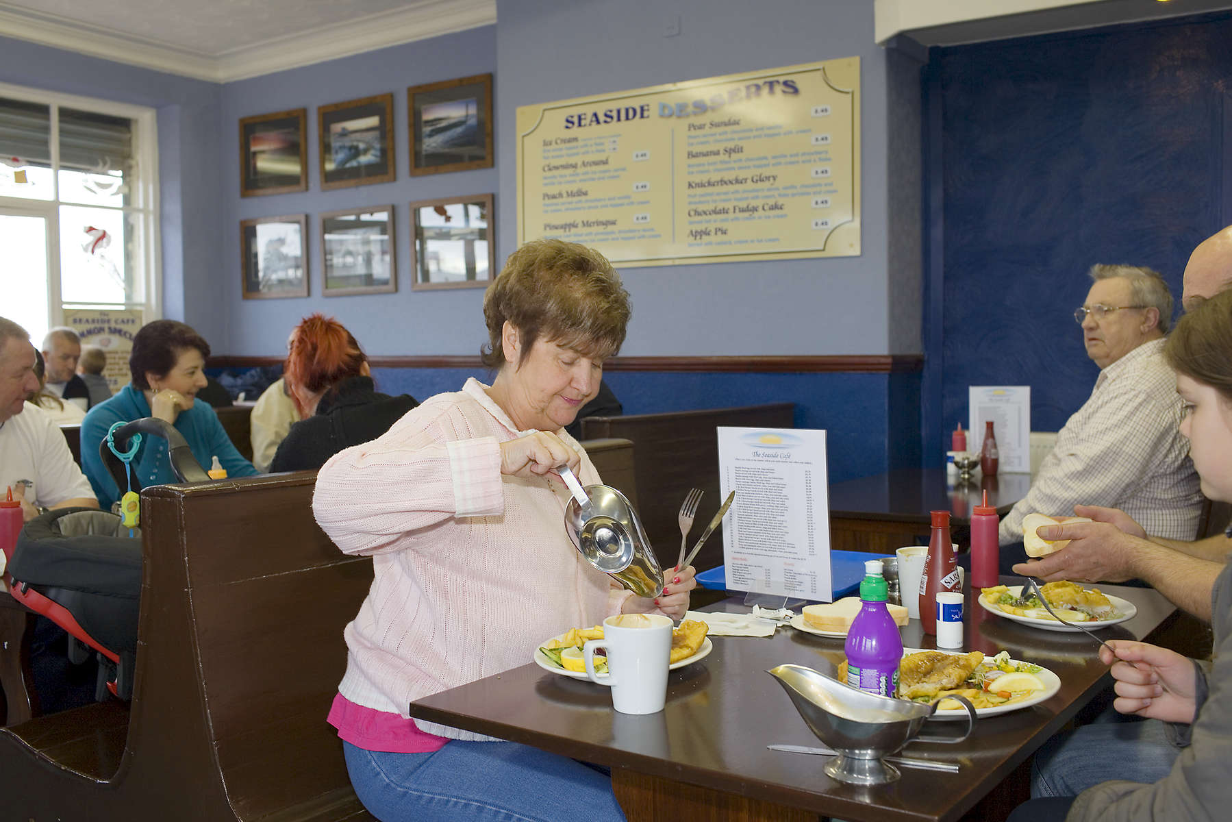 A woman pours gravy on her fis and chips served at the Seaside Cafe on Marine Promenade.In 1986 world famous photographer Martin Parr published his book 'The Last Resort,' a set of photographs taken over three seasons 1983-85 in the Liverpool suburb of New Brighton. 25 years later, pohtographer and Parr fan, Peter Dench, went on a pilgrimage to New Brigthon to walk in Parr's footsteps to document what has changed or remained the same in the seaside town.