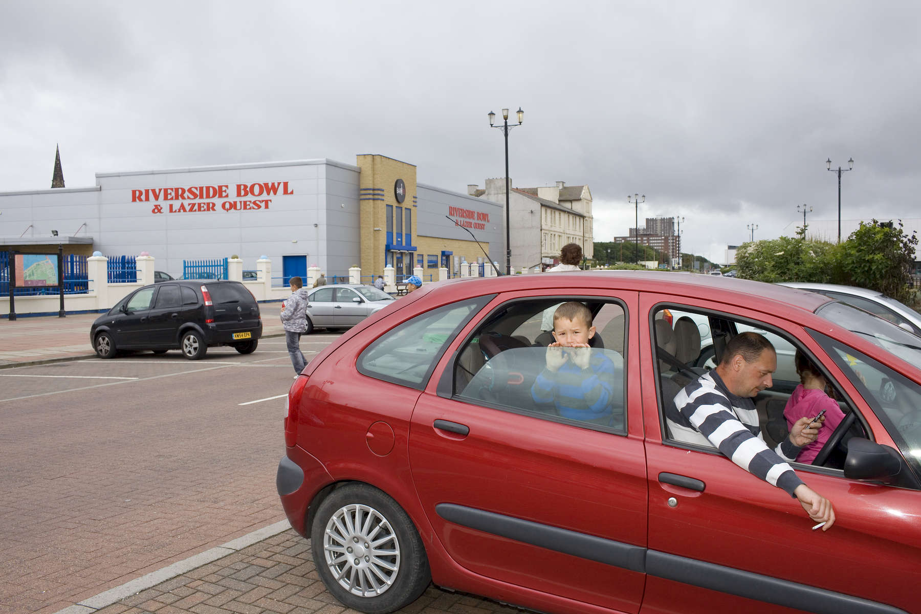 A young boy in the back seat of a car parked in front of the Riverside Bowl and Lazer Quest Centre on Marine Promenade, New Brighton.In 1986, world famous photographer Martin Parr published his book 'The Last Resort,' a set of photographs taken over three seasons 1983-85 in the Liverpool suburb of New Brighton. 25 years later, photographer and Parr fan, Peter Dench, went on a Bank Holiday pilgrimage to New Brigthon to walk in Parr's footsteps and document what has changed or remained the same in the seaside town.