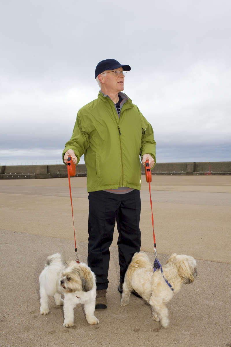 Steve out walking dogs Bobby and Rocky along King's Parade in New Brighton.In 1986, world famous photographer Martin Parr published his book 'The Last Resort,' a set of photographs taken over three seasons 1983-85 in the Liverpool suburb of New Brighton. 25 years later, photographer and Parr fan, Peter Dench, went on a Bank Holiday pilgrimage to New Brighton to walk in Parr's footsteps and document what has changed or remained the same in the seaside town.
