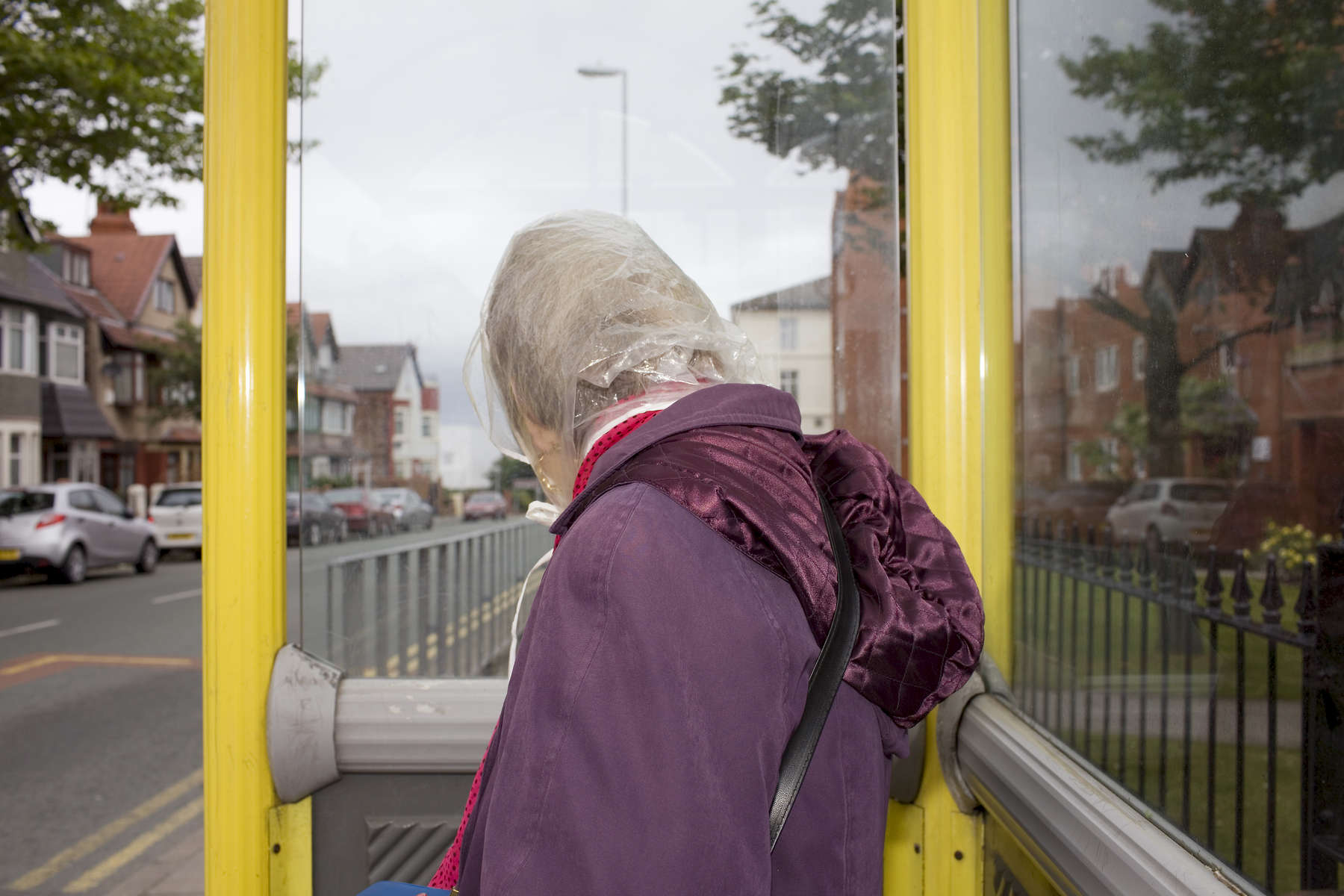 An elderly woman waits at a bus stop on Rowson Street in New Brighton.In 1986, world famous photographer Martin Parr published his book 'The Last Resort,' a set of photographs taken over three seasons 1983-85 in the Liverpool suburb of New Brighton. 25 years later, photographer and Parr fan, Peter Dench, went on a Bank Holiday pilgrimage to New Brighton to walk in Parr's footsteps and document what has changed or remained the same in the seaside town.