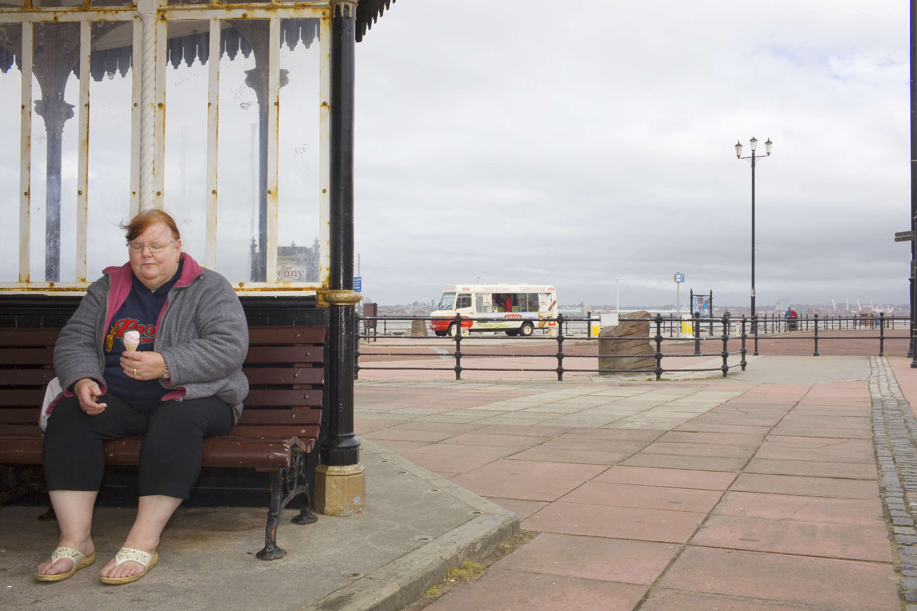 A woman sat with an ice cream in a weather shelter on Marine Promenade.In 1986, world famous photographer Martin Parr published his book 'The Last Resort,' a set of photographs taken over three seasons 1983-85 in the Liverpool suburb of New Brighton. 25 years later, photographer and Parr fan, Peter Dench, went on a Bank Holiday pilgrimage to New Brighton to walk in Parr's footsteps and document what has changed or remained the same in the seaside town.
