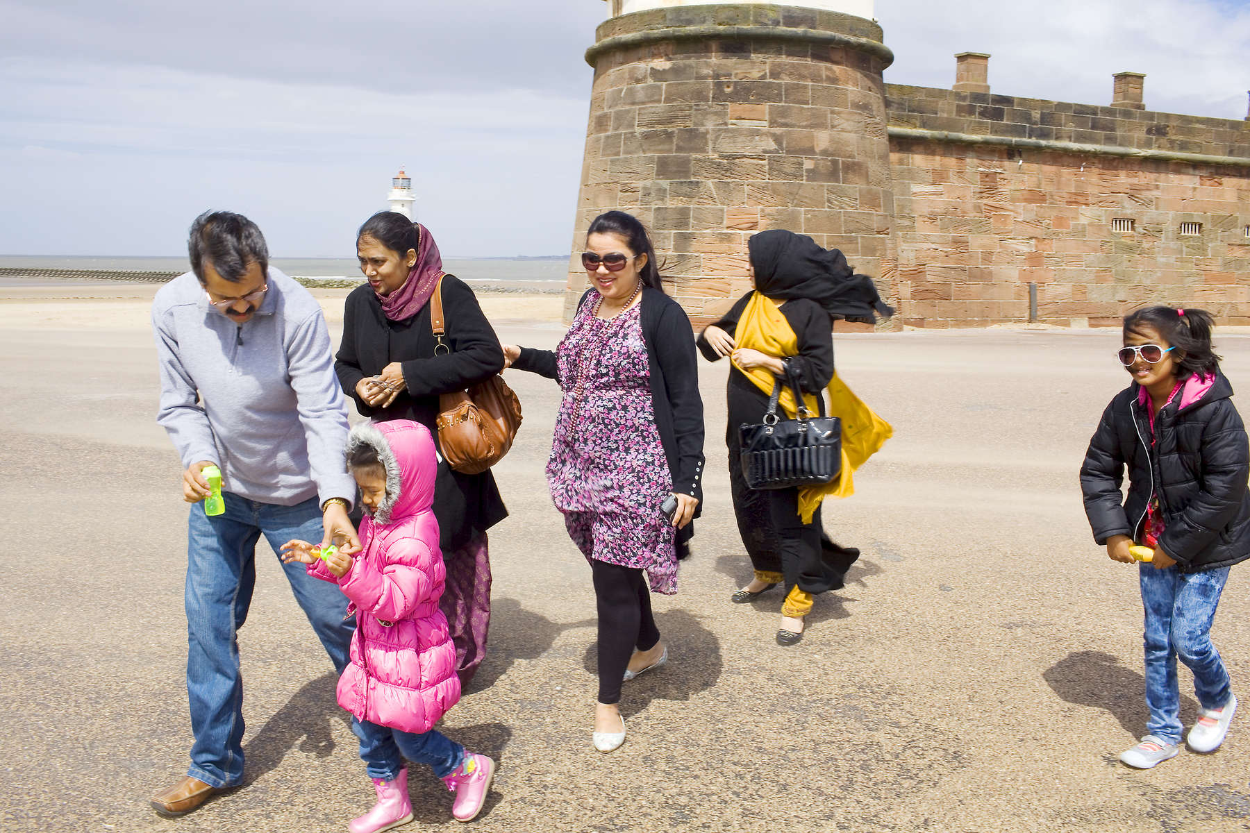 An Asian family take a walk near Fort Perch Rock, New Brighton. In 1986, world famous photographer Martin Parr published his book 'The Last Resort,' a set of photographs taken over three seasons 1983-85 in the Liverpool suburb of New Brighton. 25 years later, photographer and Parr fan, Peter Dench, went on a Bank Holiday pilgrimage to New Brighton to walk in Parr's footsteps and document what has changed or remained the same in the seaside town.