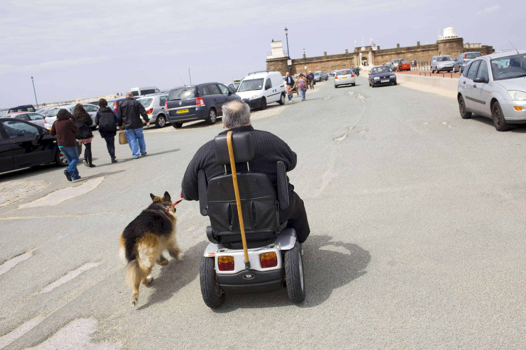 A man riding in a mobility scooter walks his Alsation Dog towards Fort Perch Rock. In 1986, world famous photographer Martin Parr published his book 'The Last Resort,' a set of photographs taken over three seasons 1983-85 in the Liverpool suburb of New Brighton. 25 years later, photographer and Parr fan, Peter Dench, went on a Bank Holiday pilgrimage to New Brighton to walk in Parr's footsteps and document what has changed or remained the same in the seaside town.