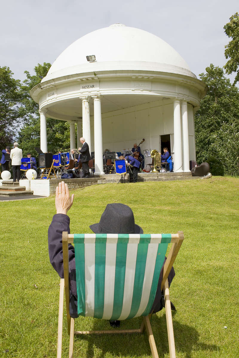 A man seated in a green and white deck chair waits for the Northwest Concert Band to perform in Vale Park.In 1986, world famous photographer Martin Parr published his book 'The Last Resort,' a set of photographs taken over three seasons 1983-85 in the Liverpool suburb of New Brighton. 25 years later, photographer and Parr fan, Peter Dench, went on a Bank Holiday pilgrimage to New Brighton to walk in Parr's footsteps and document what has changed or remained the same in the seaside town.