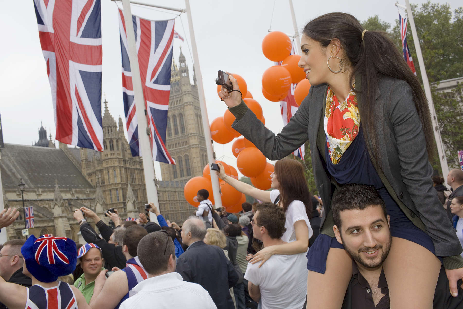 Dalia Yousif sits on the shoulders of her partner Panos to take photographs from Parliament Square of guests arriving at Westminster Abbey for the Royal Wedding.