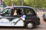 A young girl wearing a tiara waves from a black London taxi on the Mall heading towards Buckingham Palace.