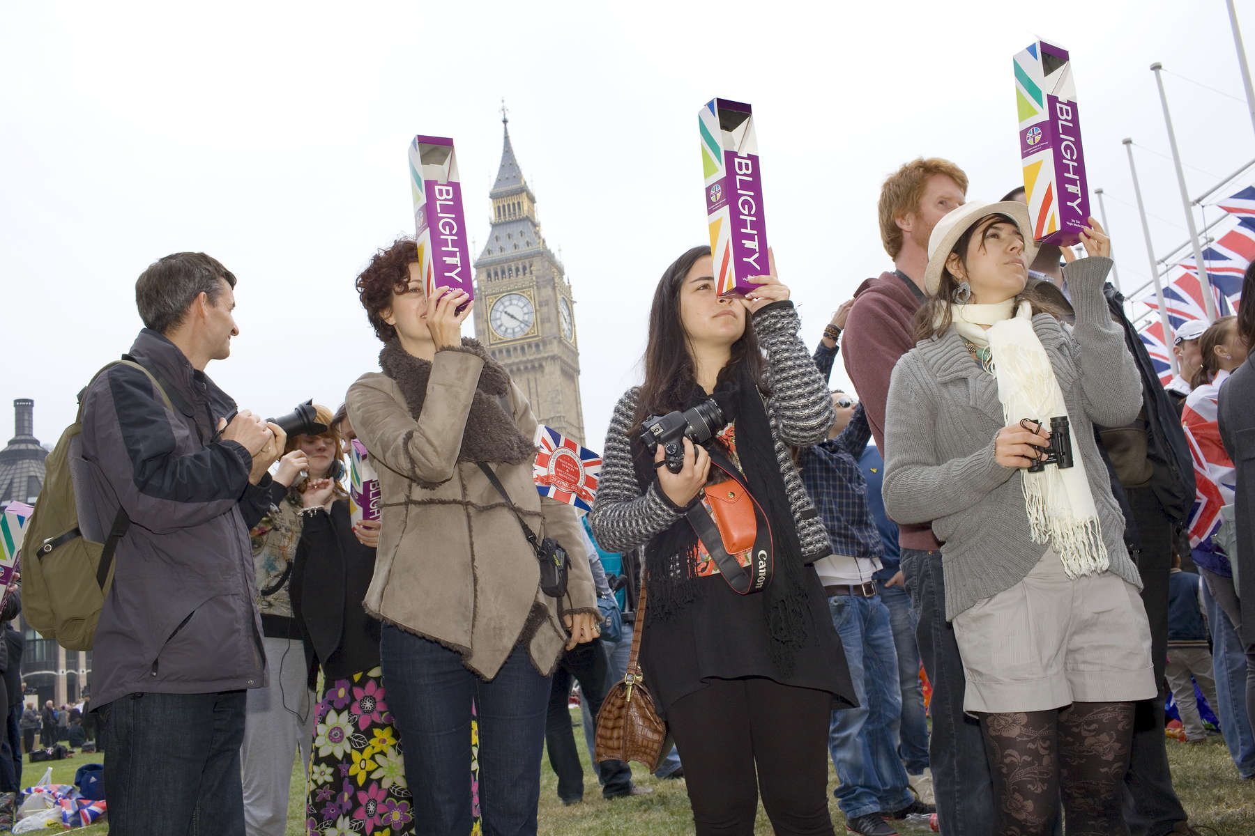 Spectators in Parliament Square watch guests arriving at Westminster Abbey with the help of a 'Blighty' periscope.