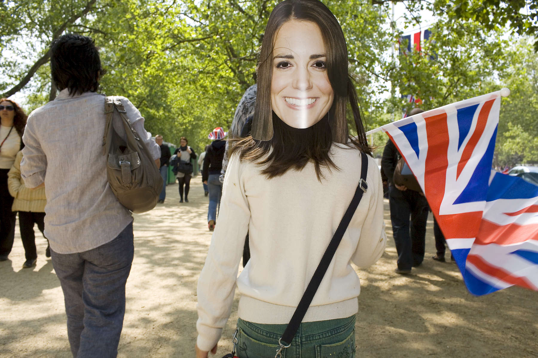A young girl with a Kate Middletom mask on the back of her head waves a union flag as she walks along the Mall towards Buckingham Palace.