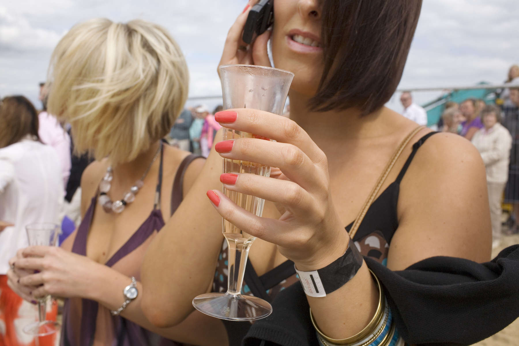 A woman talks on her mobile phone with a glass of champagne at the inaugural British beach Polo event on Sandbanks beach. Sandbanks is a small sand dune on the south coast in the county of Dorset and arguably the most expensive place to live on the planet. Property by the golden sand beach and turquoise clear sea are fetching $20 million prices.
