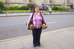 A woman carries her two Yorkshire Terrier dogs in seperate bags while on a visit to York Minster. Built between the 12th and 15th Centuries it is the largest Gothic church in England. The Yorkshire Terrier is a small dog breed of Terrier type developed in the 1800's in Yorkshire. The defining features of the breed are its small size and silky blue tan coat.