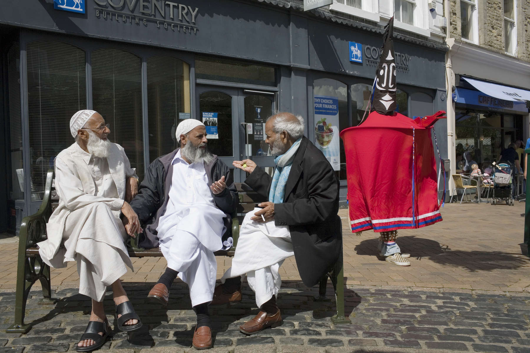 Three Muslim men chat on a bench as a Cobb's horse parades through the Oxfordshire town of Banbury as part of the annual hobby horse festival. A hobby horse is puppet-like costume giving the wearer the appearance of a man on horseback. Cobb's Horse was created in 1976 when the newly revived Adderbury Morris Men had been invited to dance at the Sidmouth Festival and one very new dancer, Stephen Wass, not yet qualified as a dancer created the beast. The name 'Cobb's Horse' comes from an Adderbury legend to the effect that the ghost of wicked Squire Cobb careers through the village in his coach pulled by phantom horses, this is one of them.