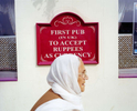 A woman walks past the Glassy Junction pub, the first in the UK to accept the indian rupee as currency.