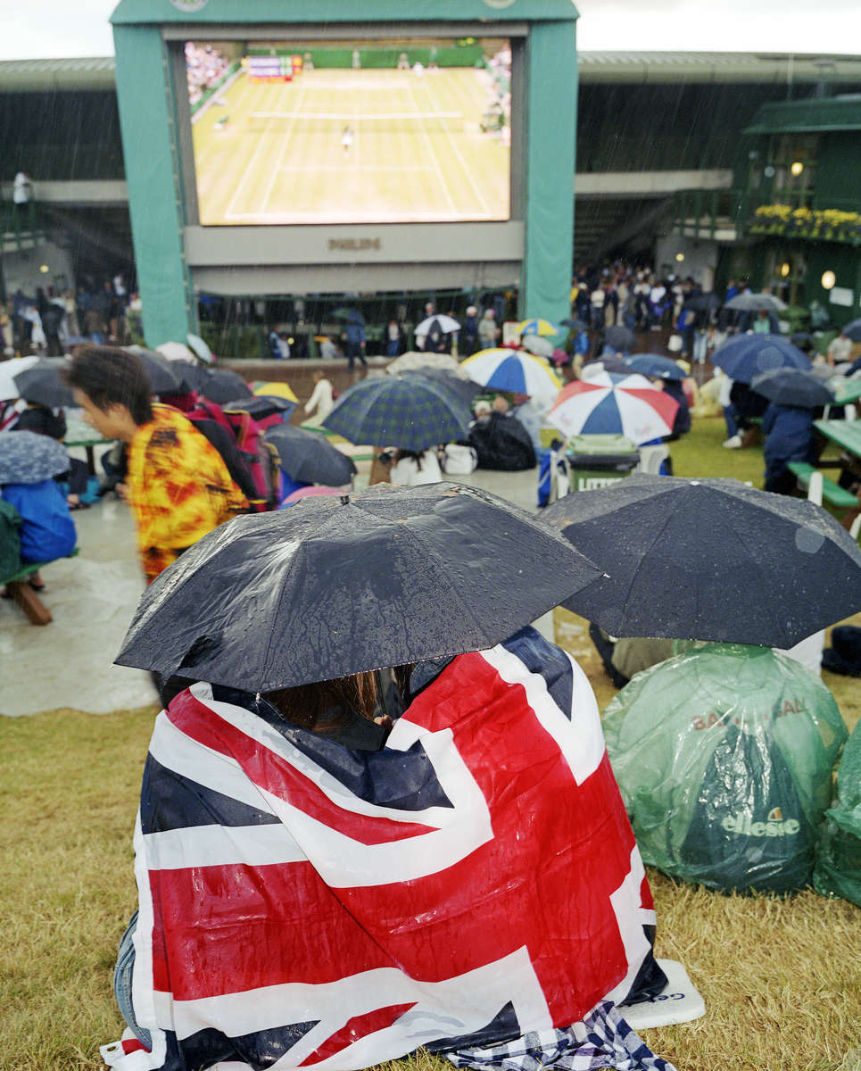 Wimbledon championship tennis fans watch the previous days play on a giant screen.