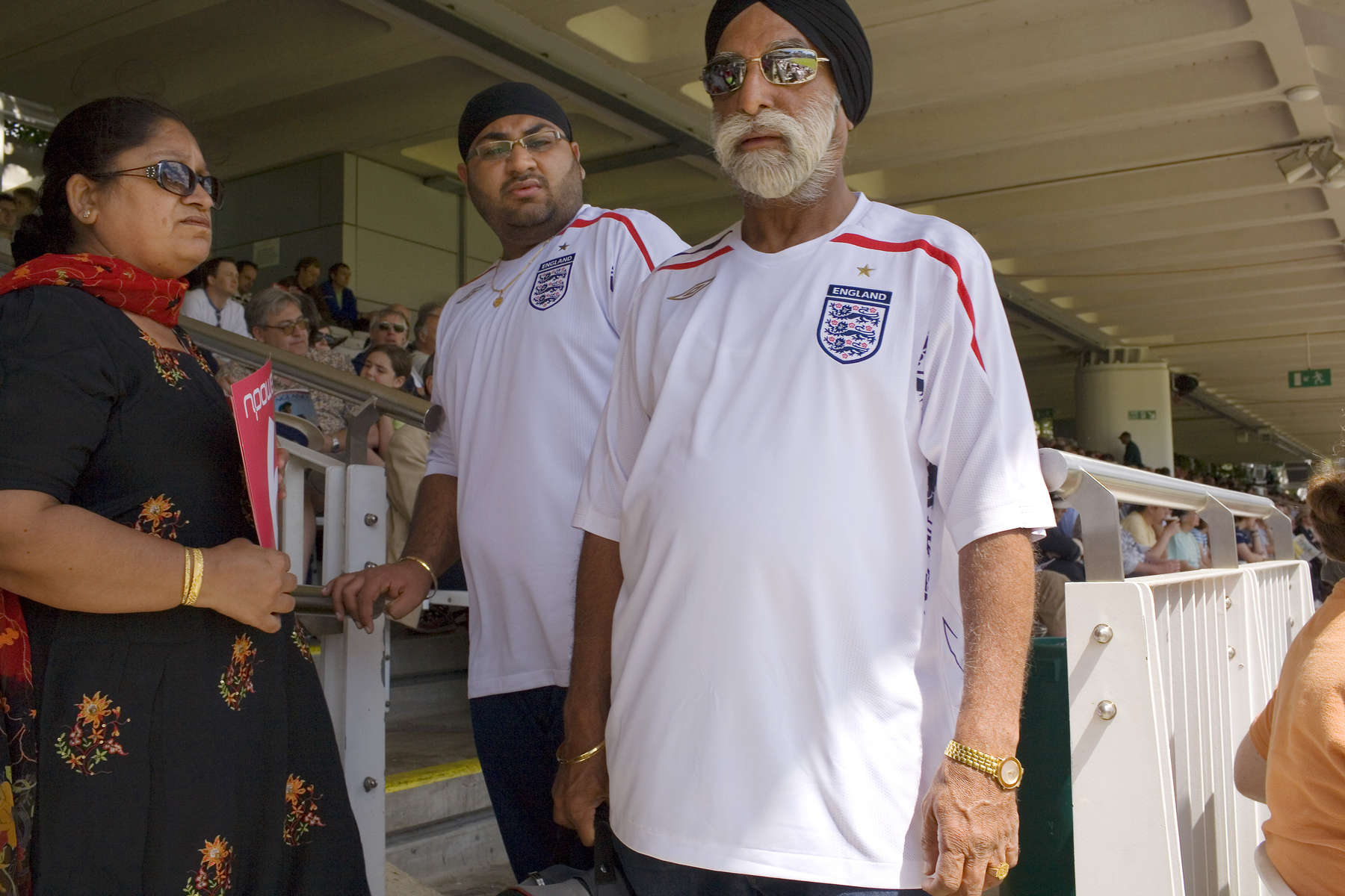 Two Asian men wearing England football shirts in the crowd at an England cricket match at Lords. Lords Cricket ground in St. John's Wood north London is recognised as the home of cricket and the games spiritual headquarters.