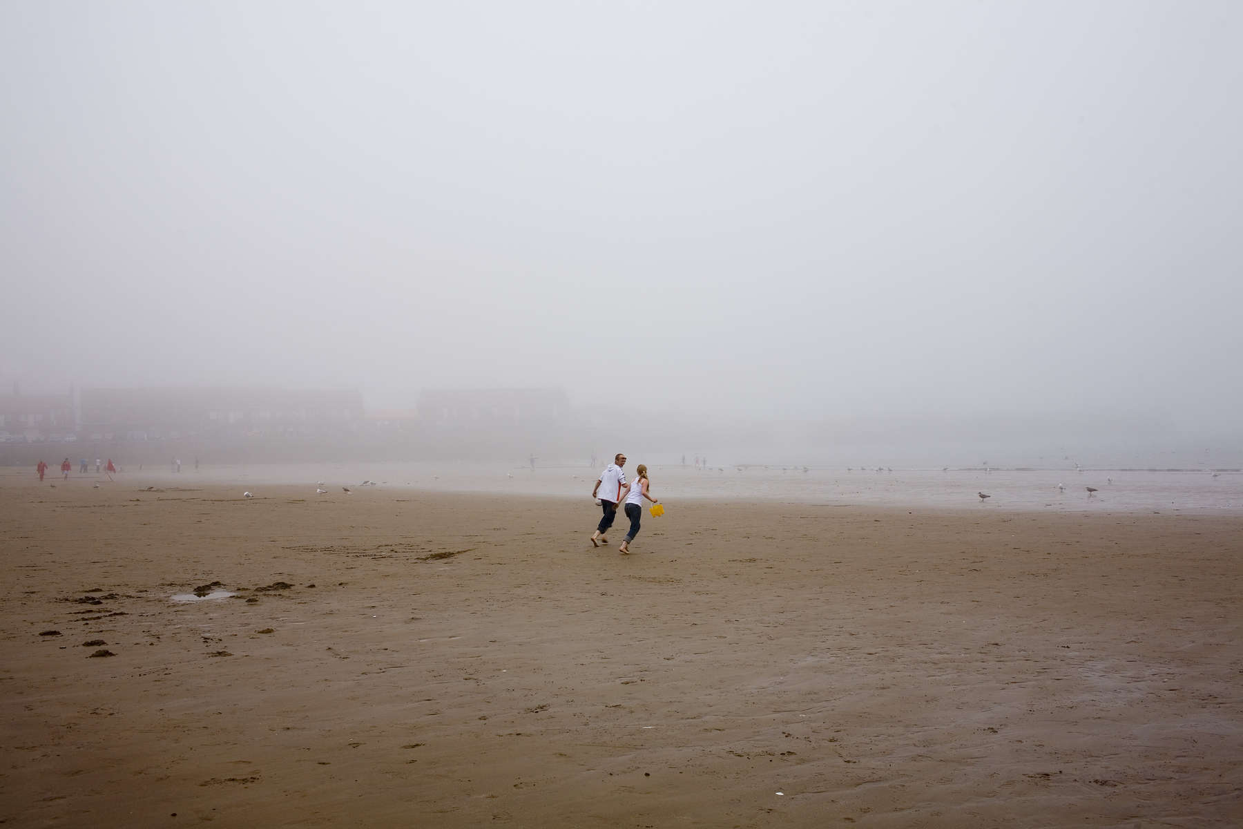 A young couple carrying a yellow bucket between them run towards the sea on a misty Scarborough beach. The Scarborough is a town on the North Sea coast of North Yorkshire that dates back to around 966AD. With a population of about 50000 Scarborough is the largest holiday resort on the Yorkshire coast. It is home to residential communities, business, fishing and service industries plua a growing digital and creative economy.