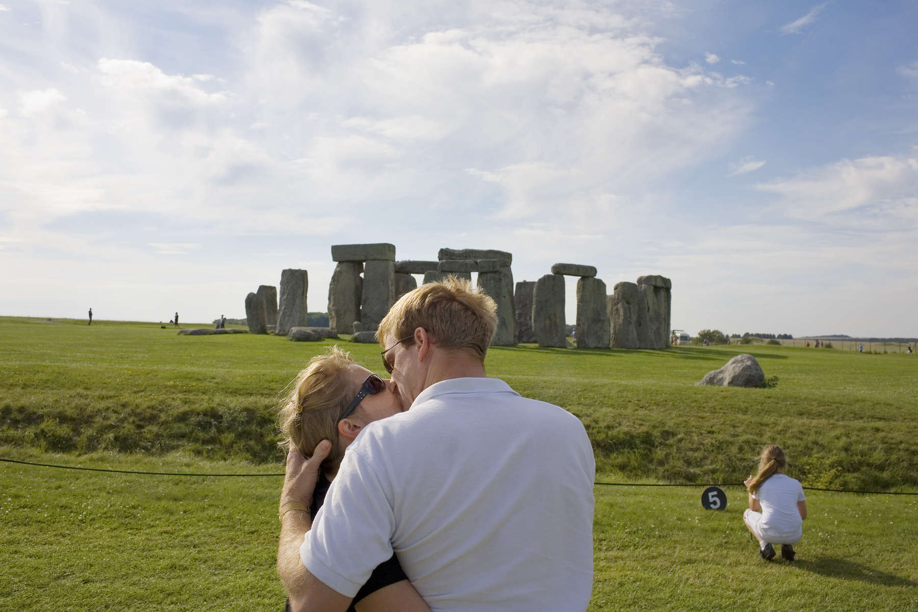 A couple share a passionate kiss in fornt of Stonehenge. Stonehenge is a prehistoric monument located in the English county of Wiltshire. One of the most famous prehistoric sites in the world, Stonehenge is composed of earthworks surrounding a circular setting of large standing stones. Archaeologists believe that the iconic stone monument was erected around 2500 BC.