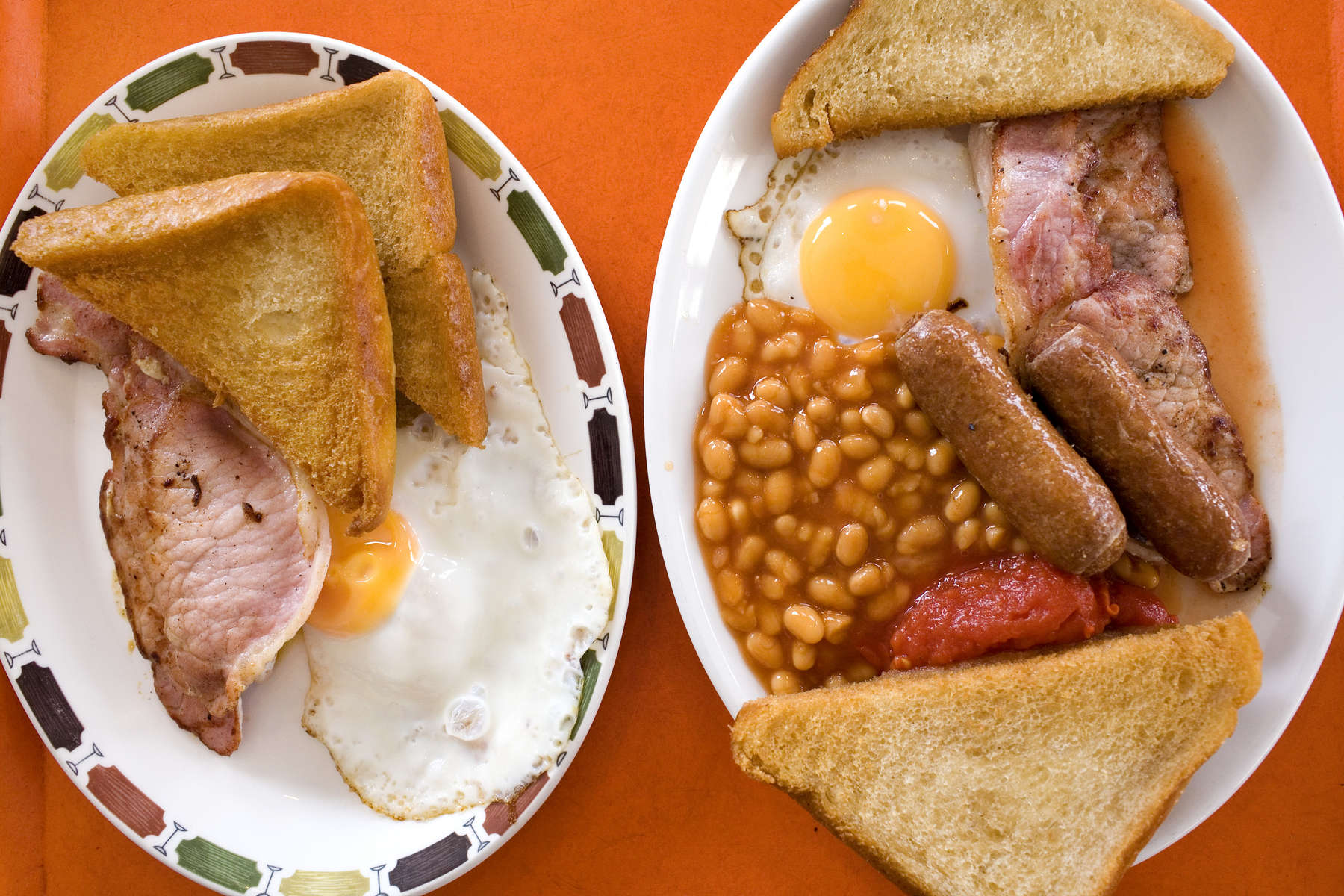 Two traditional English Breakfasts served on a tray in a cafe in Blackpool. At the heart of the breakfast is bacon and eggs and usually accompanied by a choice of fried bread, toast, tomatos, beans and mushrooms.