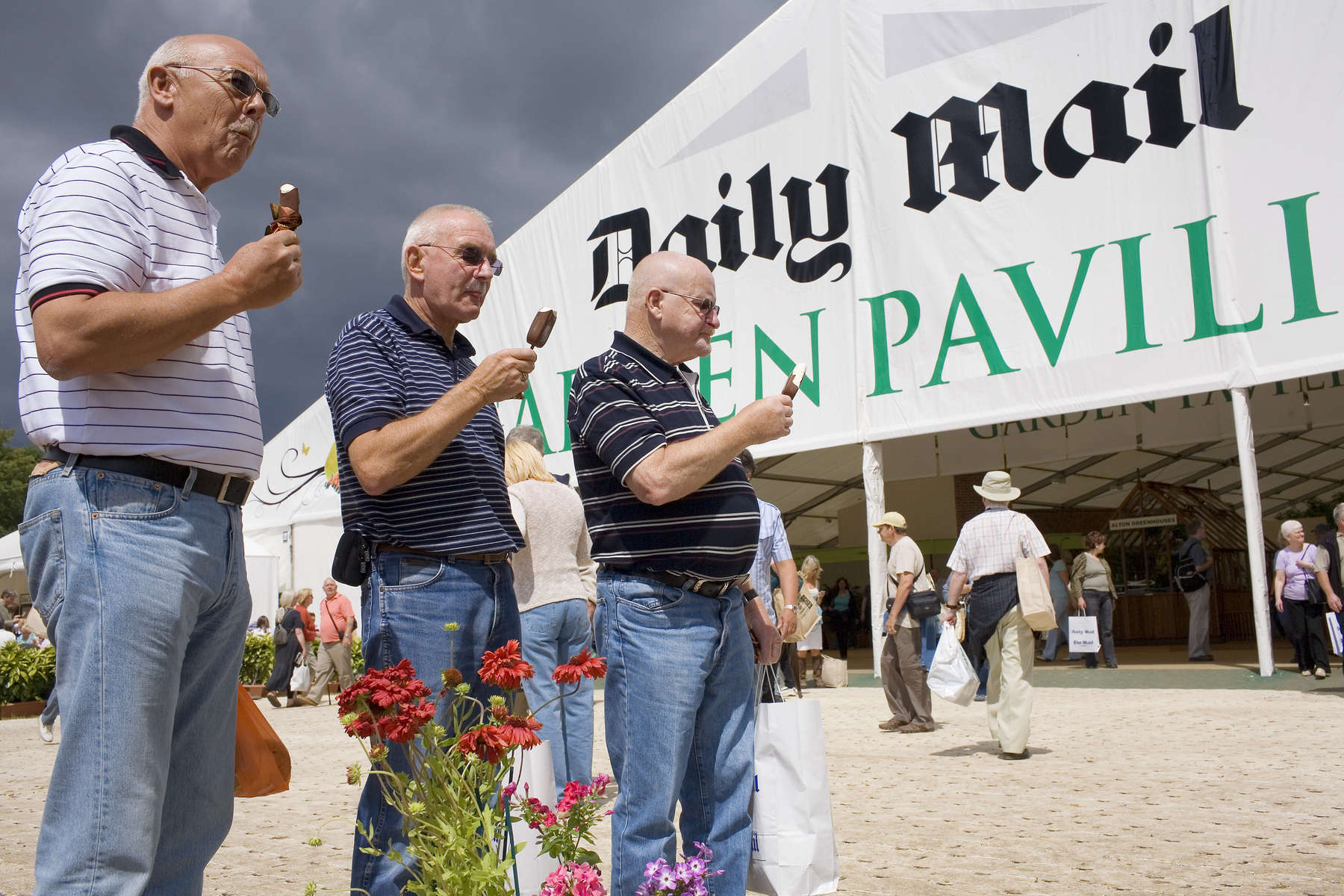 Three men eat ice creams as they wait with a bag of plants for their partners outside the Daily Mail sponsored marquee at the Hampton Court Palace annual Royal Horticultural Society summer flower show. Hampton Court Palace is a former royal palace in the London Borough of Richmond Upon Thames. Thomas Wolsey, then Archbishop of York and Chief Minister to the King took over the lease in 1514 and rebuilt the 14th Century manor house over the next 7 years (1515-1521) to form the nucleus of the present palace before Henry VIII took it as his residence.