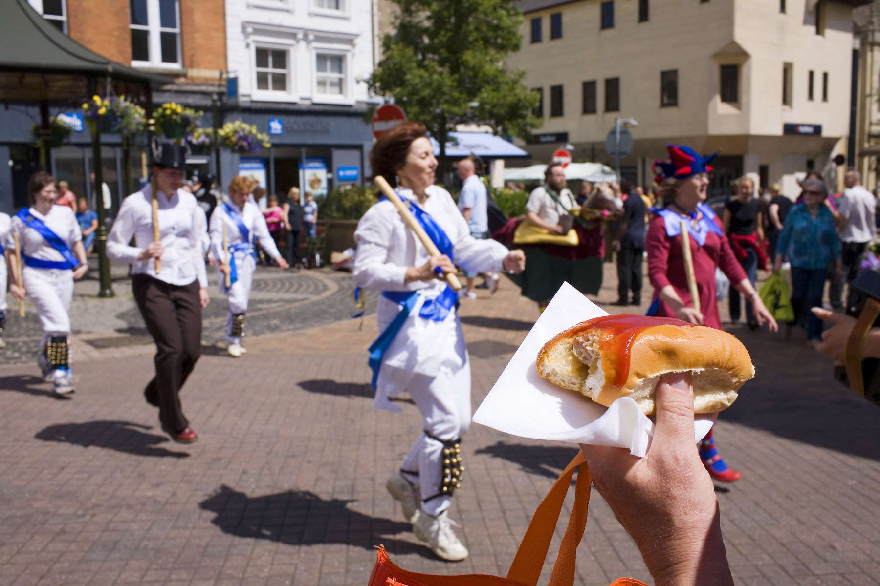 A man with a hot dog watches Morris-Women perform in Banbury town centre as part of the Hobby Horse festival. A hobby horse is a puppet-like costume giving the wearer the appearance of a man with a horse. For centuries hobby horses, Jack in the Greens, straw men and other characters brought life and colour to civic processions in towns and cities across the country, many of them can be seen in carvings in local churches. The Oxfordshite town of Banbury revived the tradition of a procession through the town in 2000. Banbury's history goes back to Anglo-Saxon times. An earlier charter from Queen Mary in 1554 had officially established Banbury as a town.