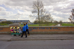 {quote}Smile 2moro will be worse{quote} - Two childcare workers push a buggy with six chidren in past a slogan spray painted on a bridge along Portobello Road on the Preston Road Estate in Hull.Kingston Upon Hull is a city in Yorkshire with a resident population of 257,000 located 25 miles from the North Sea on the River Hull at its junction with the Humber estuary. Hull suffered heavy damage during the Second World War and went into decline suffering a wide range of social deprivation. Recently the city has embarked on a programme of regeneration and renewal.Photographer: Peter Dench+44(0)7711058090 peter@peterdench.comPhotography © Peter Denchcommissioned by:Dagmar Seeland London officeHarald Menk Hamburg office
